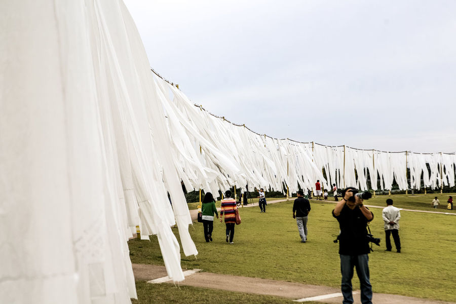 Art Clear Sky Covering Day Fabric Famous Place Famous Places Full Length Imjingak Incidental People Leisure Activity Lifestyles Men Outdoors Paju Park Real People Rope Taking Photos Textile Transportation Travel Walking Wind Women