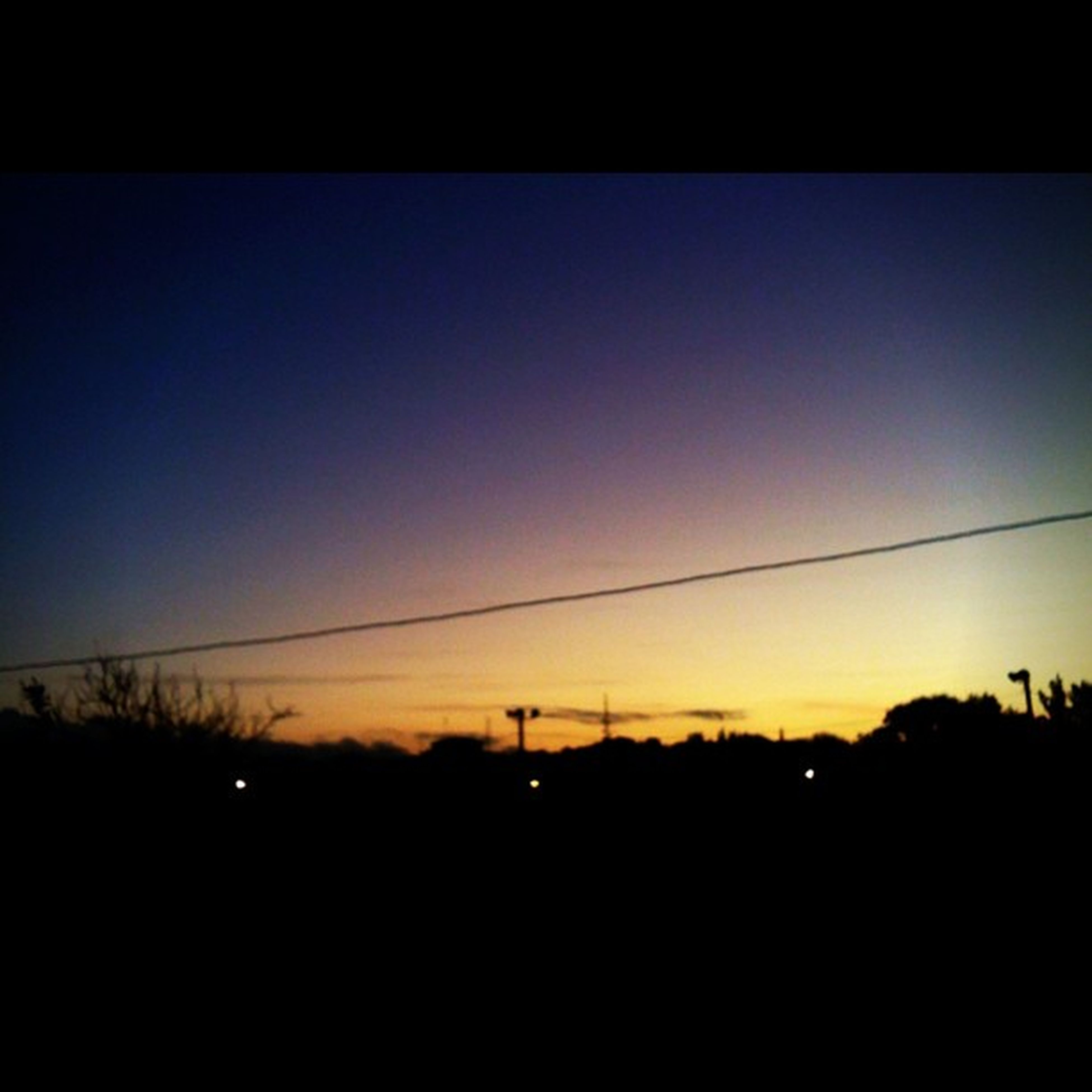 sunset, silhouette, power line, orange color, scenics, tranquility, beauty in nature, tranquil scene, sky, copy space, dark, electricity pylon, nature, outline, clear sky, dusk, electricity, landscape, connection, idyllic
