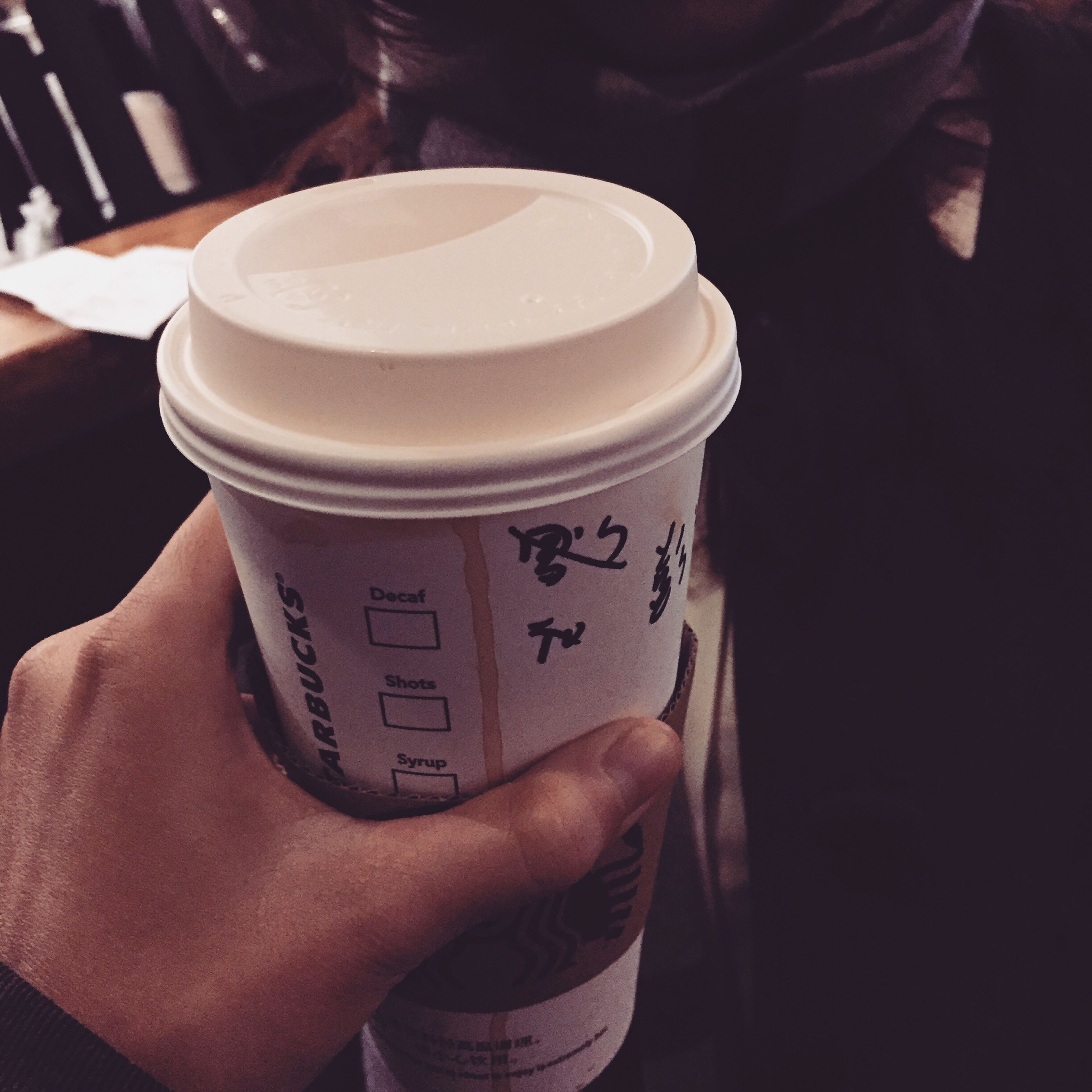 text, person, communication, western script, indoors, holding, drink, coffee cup, food and drink, refreshment, close-up, part of, coffee - drink, lifestyles, cropped, unrecognizable person, human finger