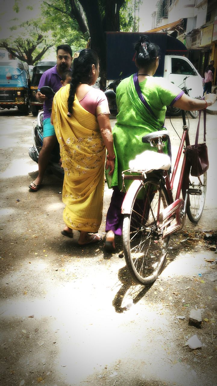 transportation, mode of transport, real people, men, bicycle, full length, traditional clothing, street, land vehicle, togetherness, yellow, cultures, outdoors, women, day, stationary, celebration, built structure, road, lifestyles, building exterior, standing, sari, boys, architecture, city, tree, young adult, bride, adult, people