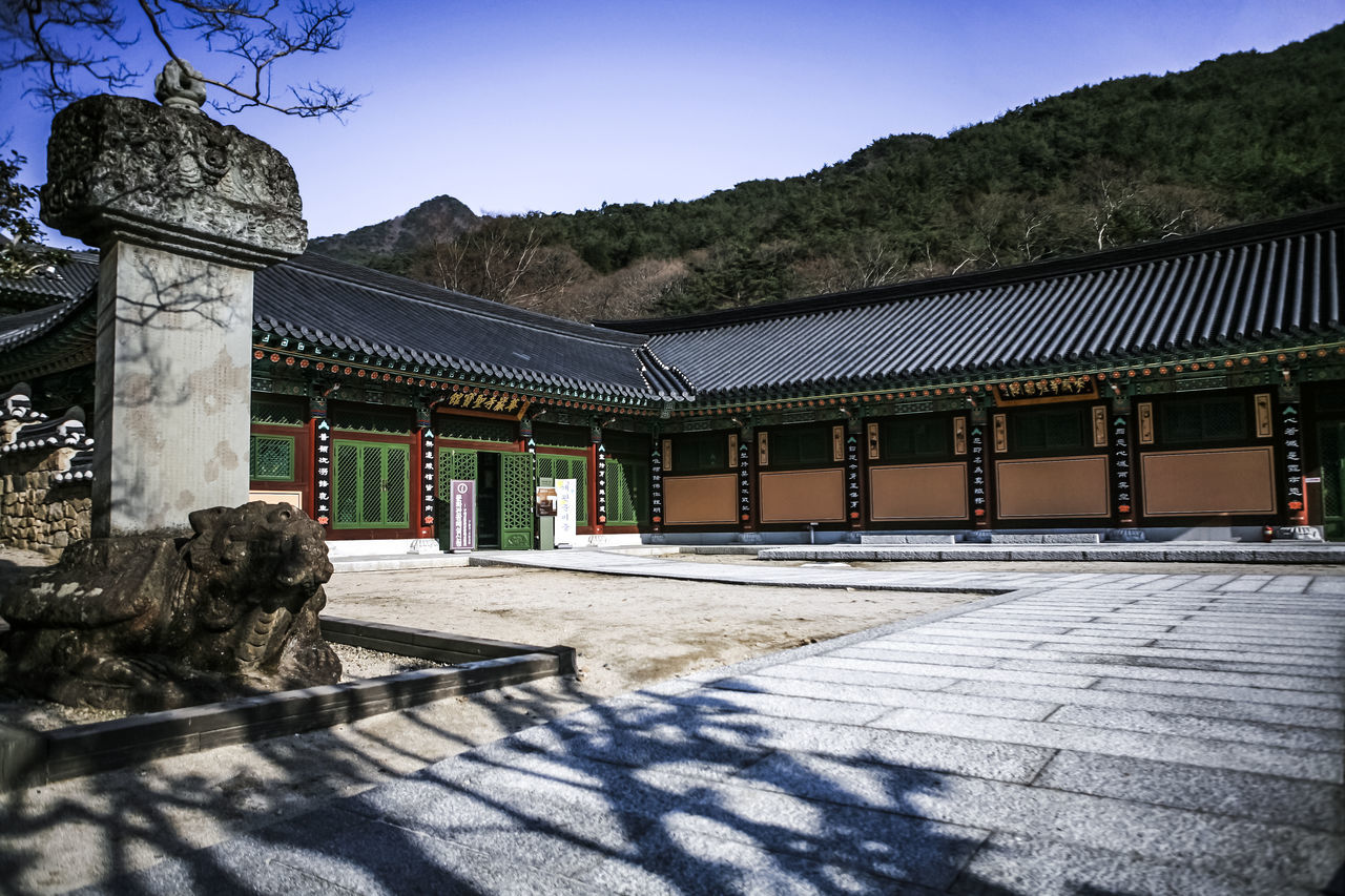 architecture, built structure, building exterior, day, outdoors, sunlight, sky, mountain, no people, place of worship, shadow, sculpture, tree, statue, clear sky, nature