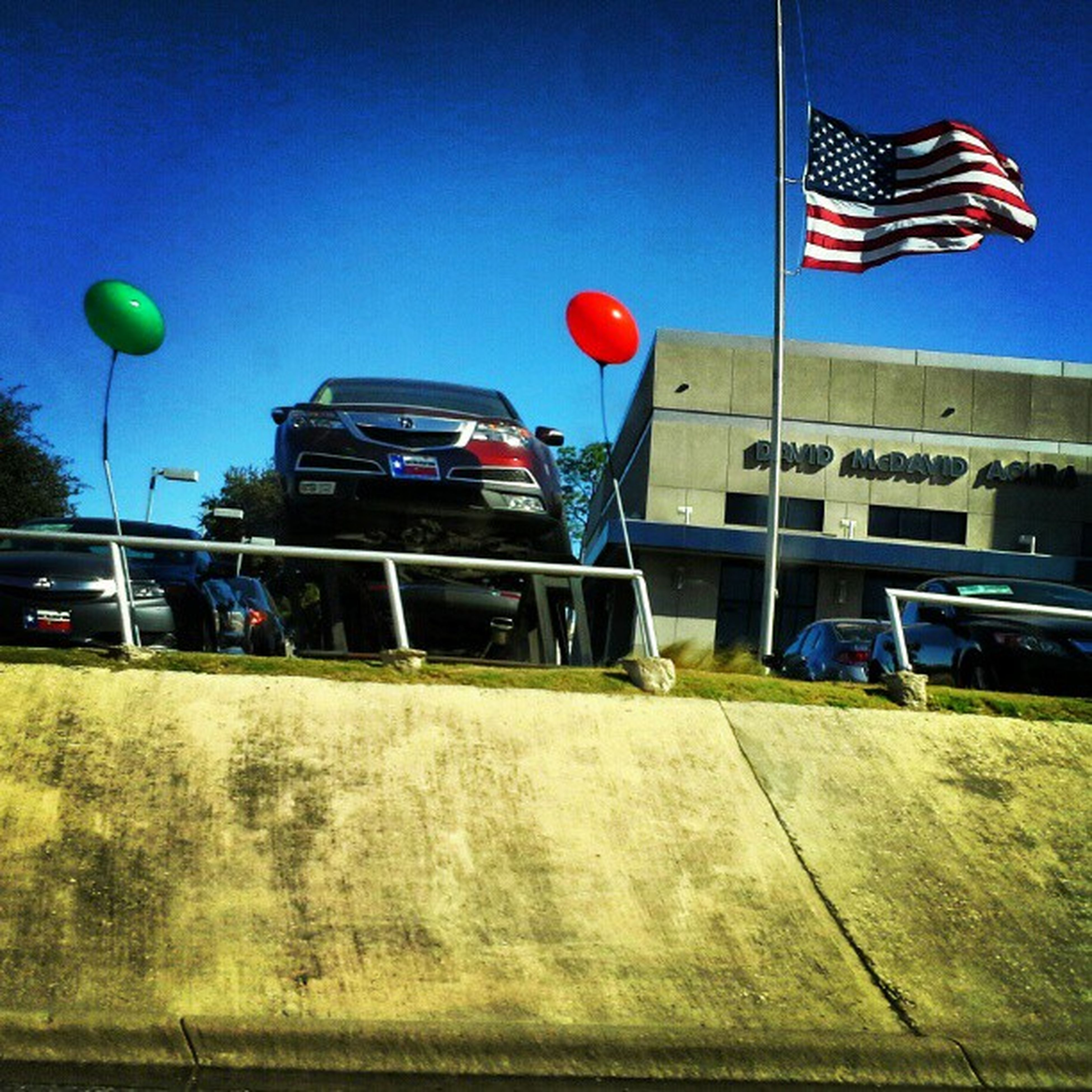 transportation, clear sky, blue, mid-air, building exterior, flag, mode of transport, sky, flying, built structure, hot air balloon, multi colored, balloon, low angle view, patriotism, copy space, sport, architecture, street light, american flag