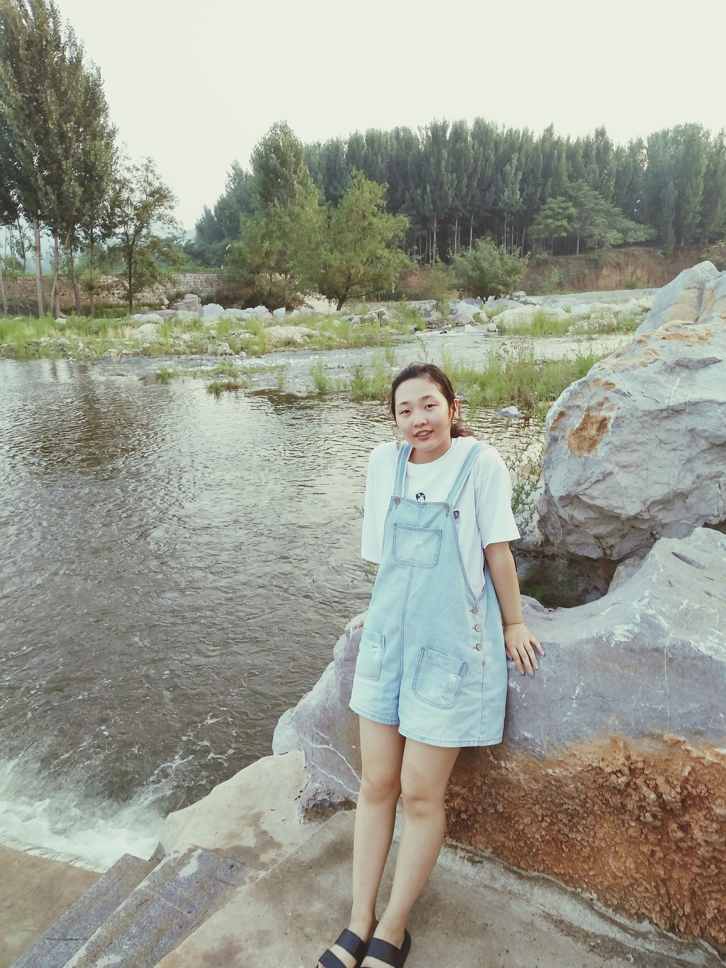 looking at camera, full length, one person, young adult, tree, portrait, young women, water, real people, day, front view, standing, outdoors, smiling, beautiful woman, lake, casual clothing, nature, leaning, leisure activity, happiness, one young woman only, sky, people