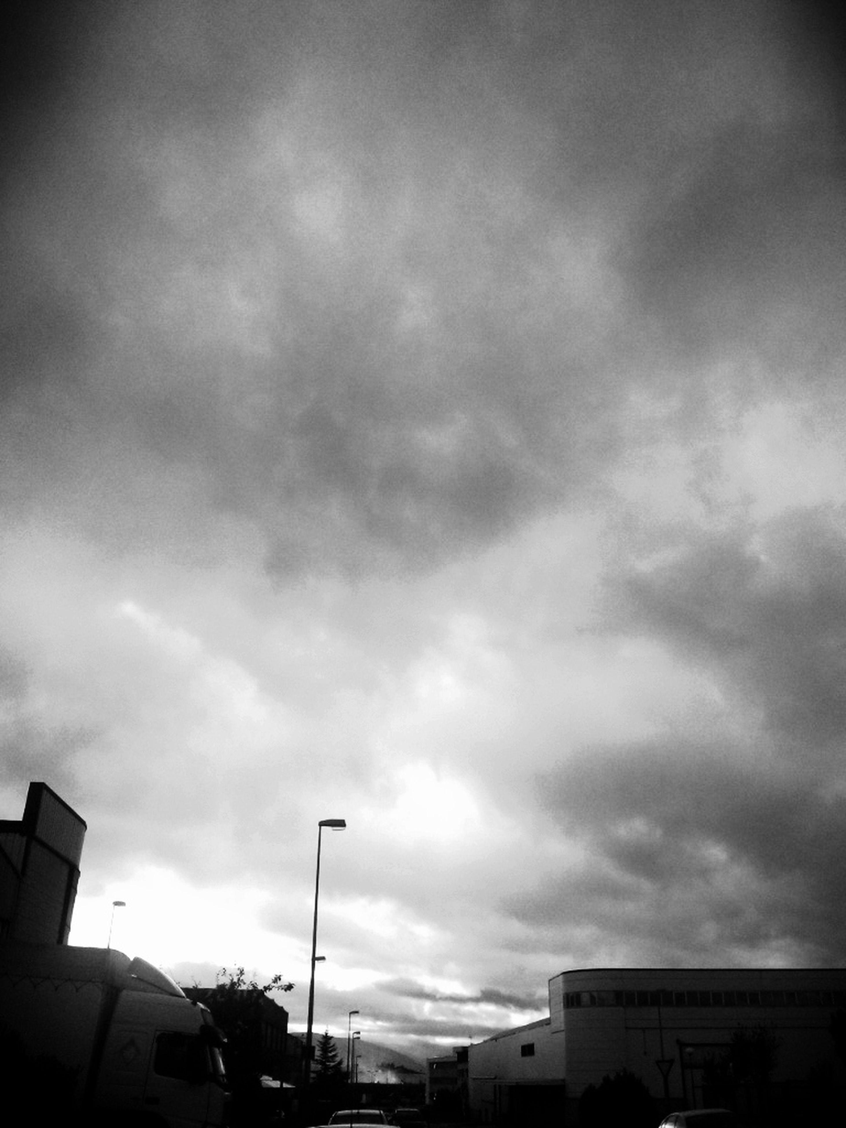 building exterior, sky, architecture, built structure, low angle view, cloud - sky, cloudy, city, building, cloud, overcast, weather, street light, residential building, silhouette, residential structure, high section, dusk, outdoors, storm cloud