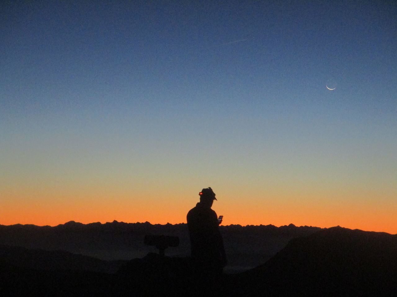 silhouette, sunset, real people, nature, clear sky, copy space, beauty in nature, standing, sky, moon, tranquil scene, scenics, leisure activity, outdoors, tranquility, lifestyles, one person, landscape, mountain, night, people