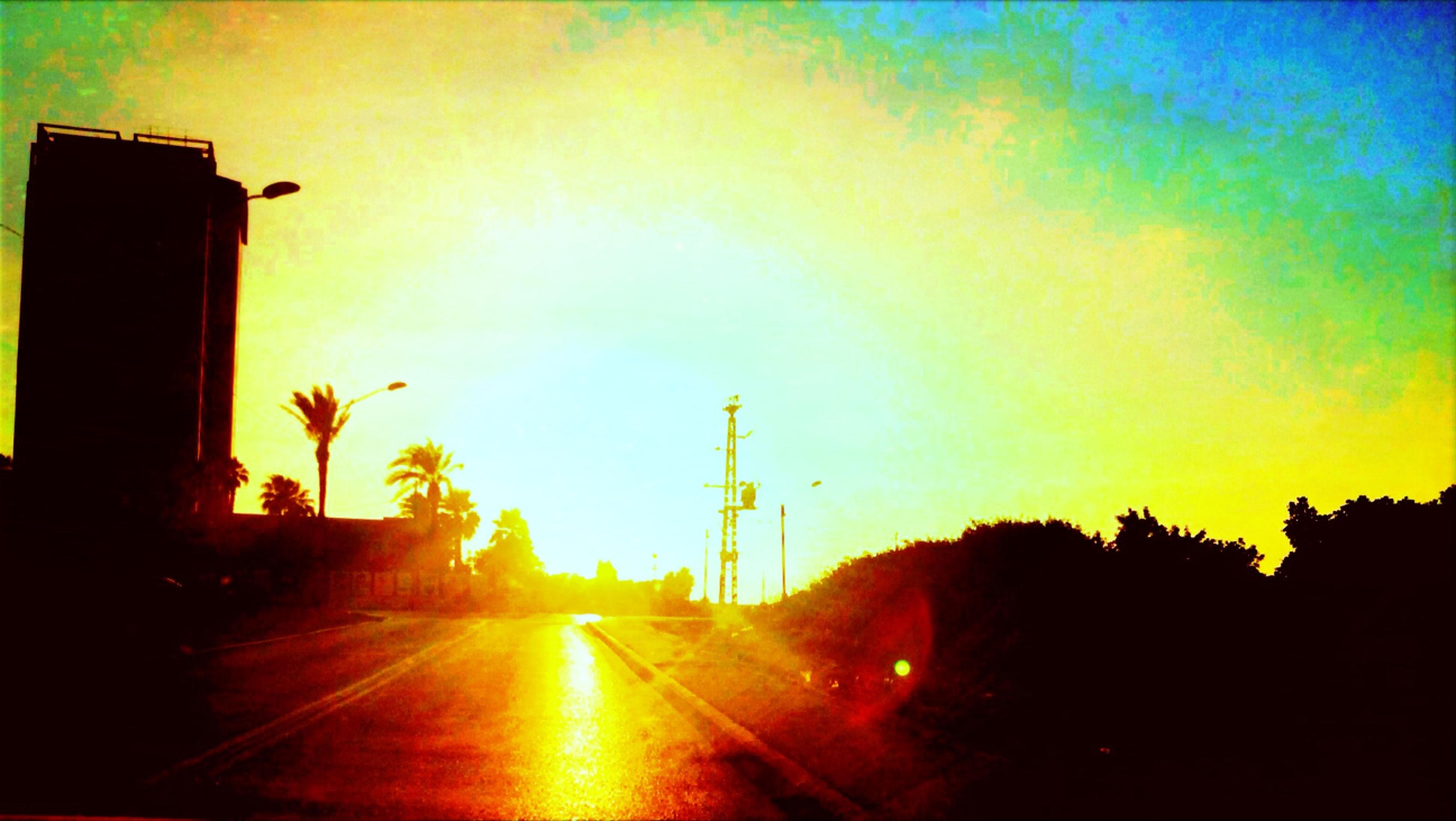 sunset, silhouette, sun, sky, building exterior, built structure, road, architecture, sunlight, the way forward, street light, sunbeam, orange color, street, lens flare, transportation, cloud - sky, tree, nature, outdoors
