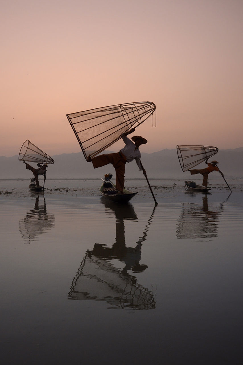 water, full length, fishing net, nature, reflection, occupation, sunset, fisherman, beauty in nature, real people, sky, waterfront, outdoors, men, lake, one person, mode of transport, nautical vessel, standing, holding, salt flat, salt basin, scenics, horizon over water, fishing equipment, working, day