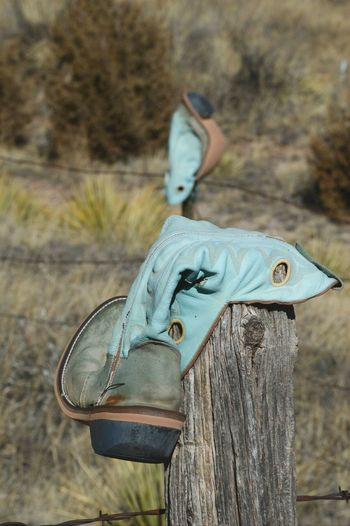Two make a pair Turquoise Old Leather Upsidedown Rural Graveyard Cowboy Boot Fence Post Barbed Wire No People Day Outdoors