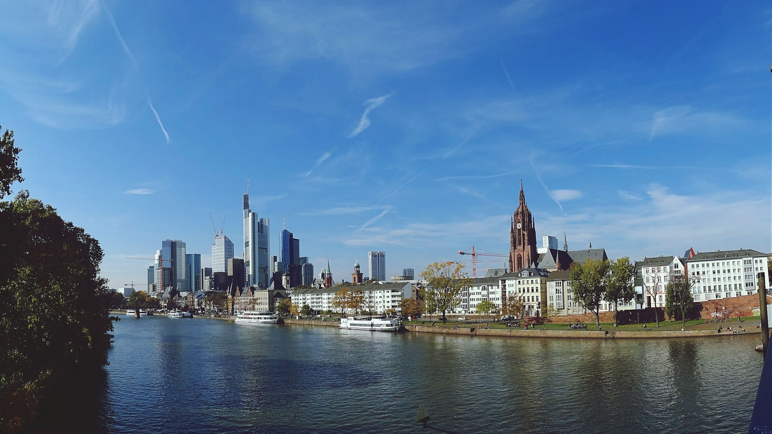 architecture, building exterior, built structure, water, city, waterfront, sky, river, nautical vessel, cityscape, transportation, capital cities, travel destinations, tower, famous place, blue, cloud - sky, travel, mode of transport, tall - high