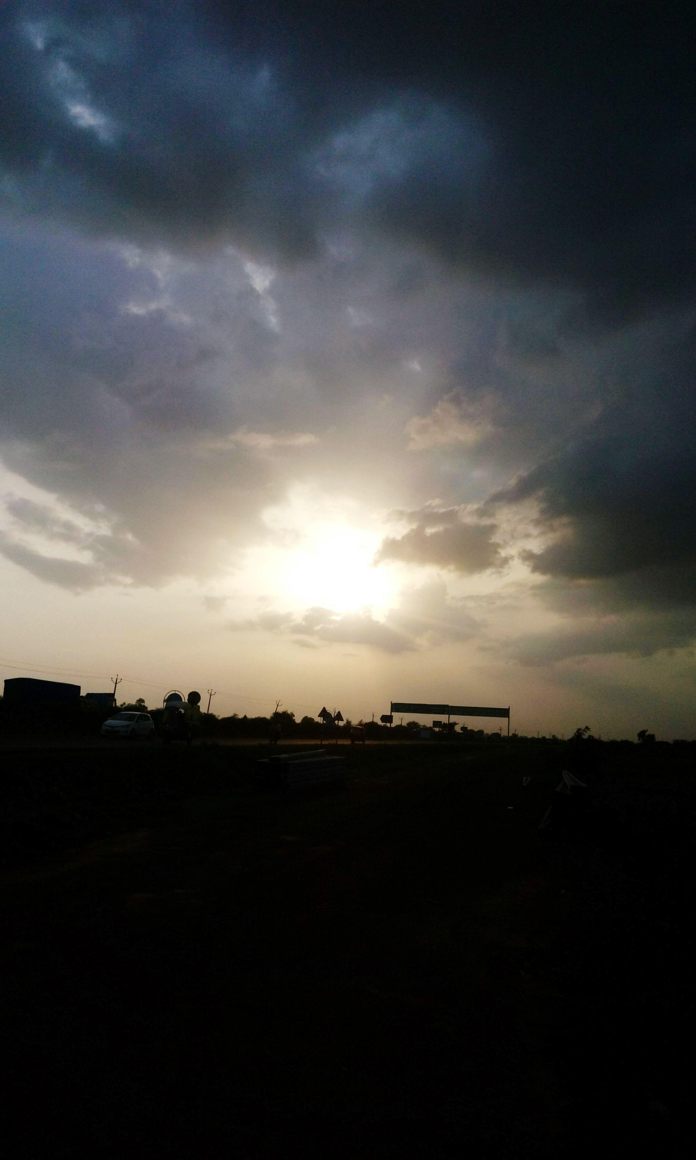 sky, sunset, cloud - sky, silhouette, sun, cloudy, scenics, tranquility, tranquil scene, beauty in nature, nature, cloud, sunlight, sunbeam, transportation, outdoors, idyllic, sea, weather, landscape