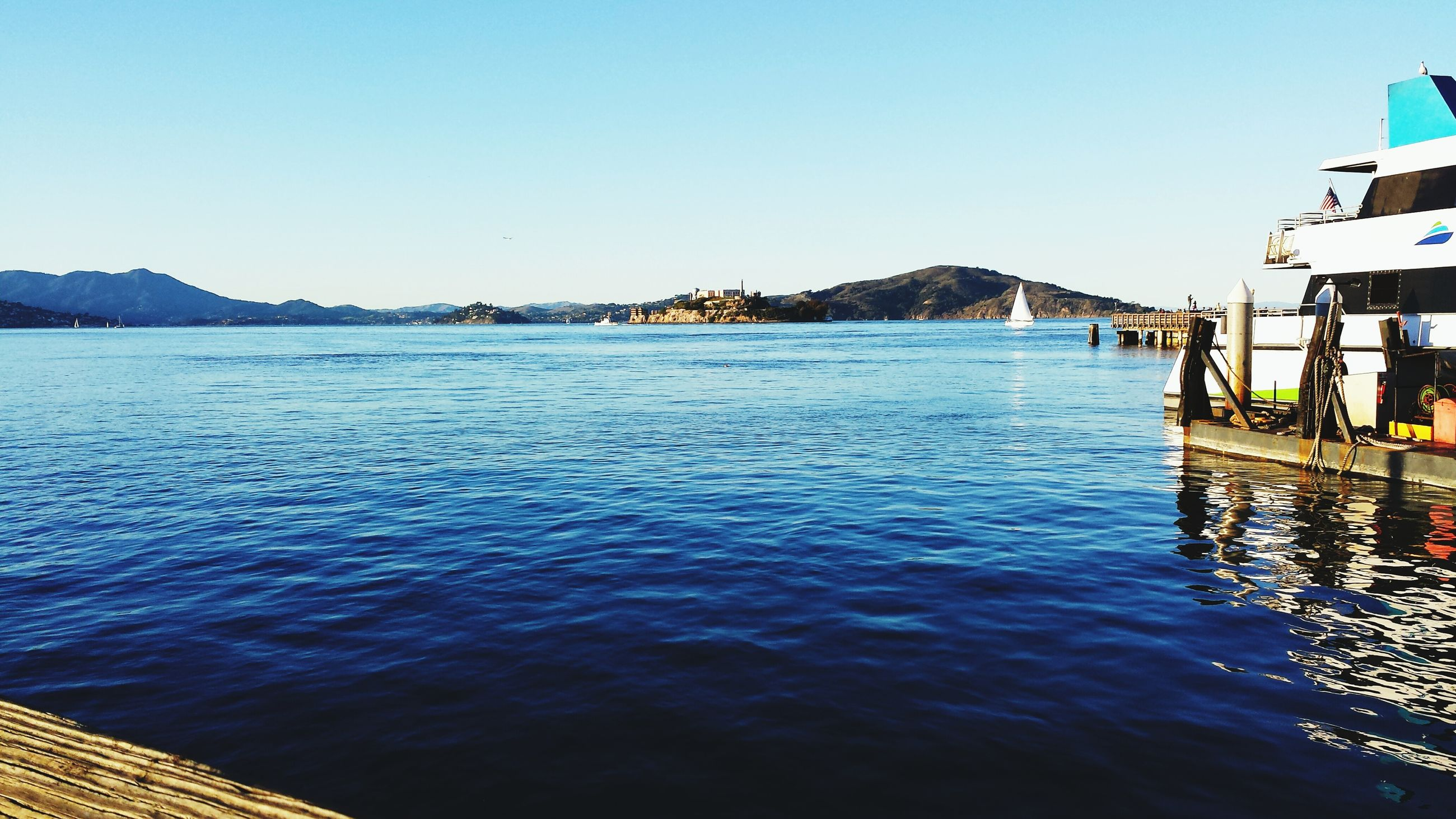 water, clear sky, mountain, blue, sea, copy space, built structure, scenics, tranquil scene, architecture, tranquility, waterfront, building exterior, beauty in nature, rippled, mountain range, nature, lake, day, idyllic