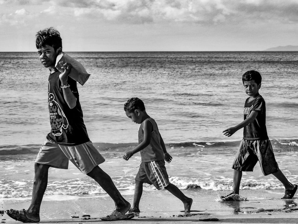 EyeemPhilippines Beach Sea Real People Sand Boys Horizon Over Water Water Full Length Outdoors Stare Philippines Journalism Sunny Blackandwhite PassingBy Walking Around Shoreline