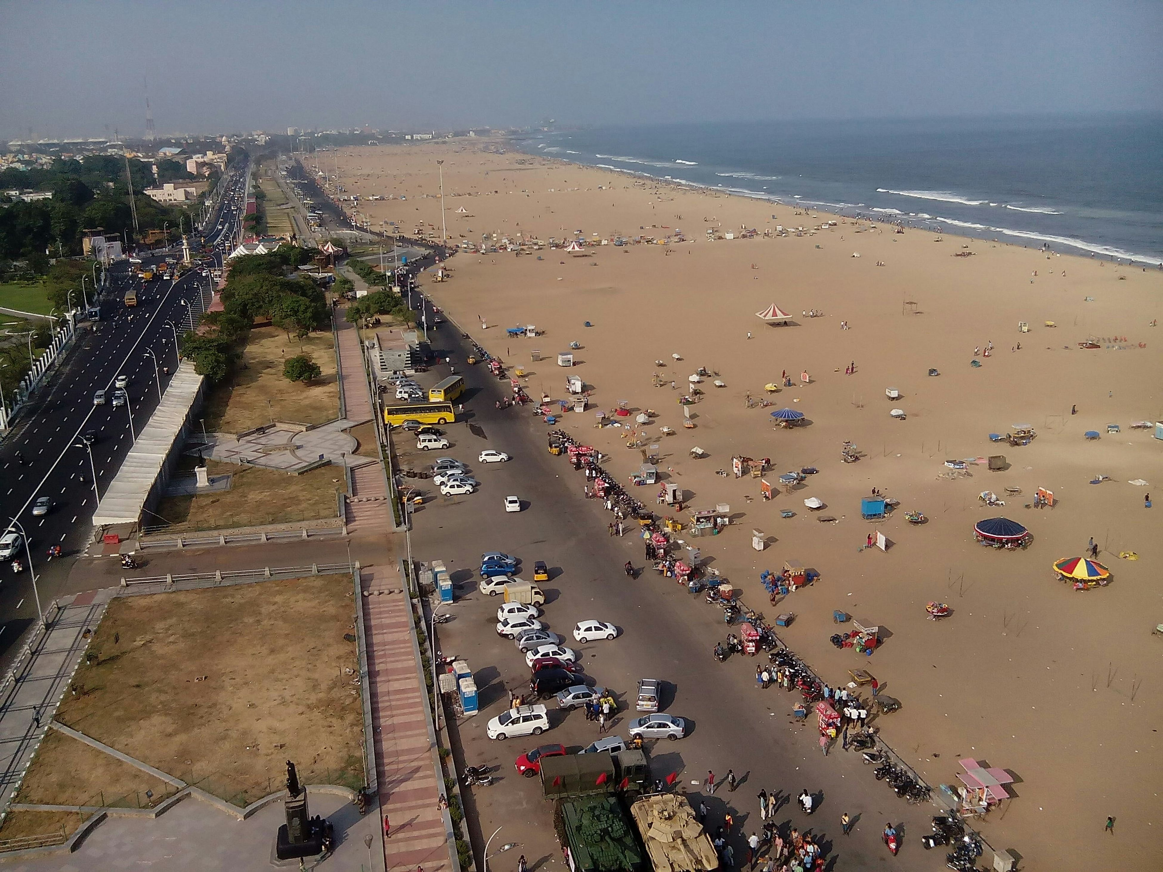 sea, beach, water, shore, horizon over water, sand, high angle view, vacations, nature, incidental people, large group of people, coastline, sky, beauty in nature, scenics, tranquility, clear sky, outdoors, day, sunlight