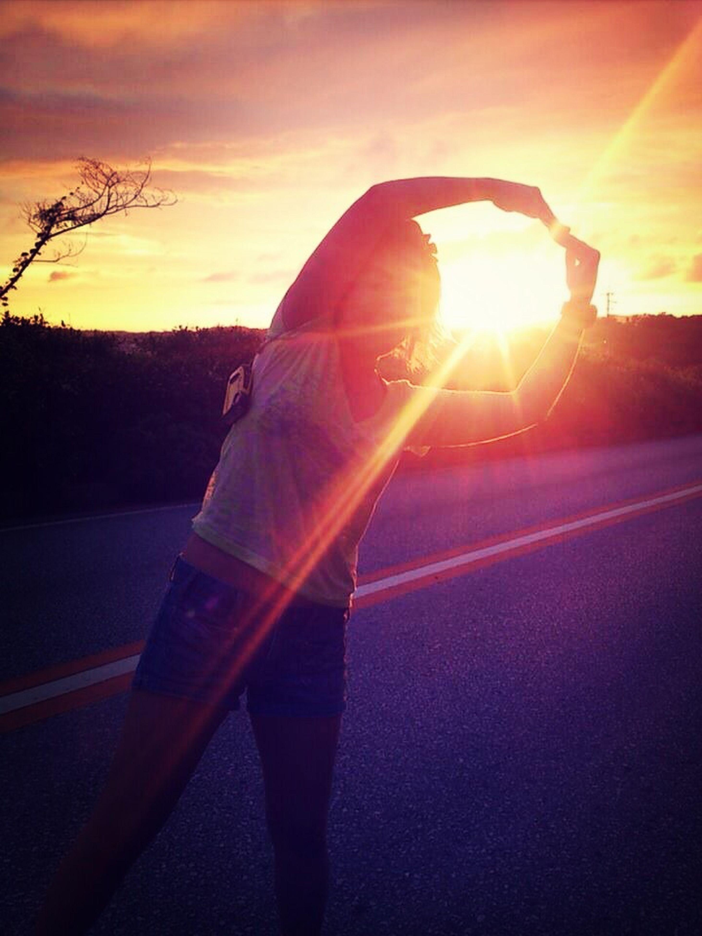 sunset, sun, sunbeam, lens flare, orange color, transportation, sunlight, sky, lifestyles, leisure activity, men, road, silhouette, car, rear view, tree, street, unrecognizable person