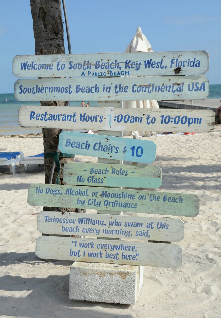 text, western script, beach, sand, communication, day, no people, outdoors, blue, close-up, nature