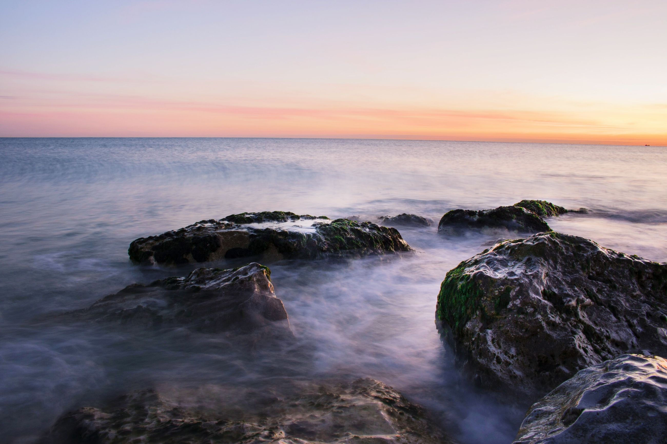 sea, sunset, scenics, water, horizon over water, beauty in nature, tranquil scene, idyllic, rock - object, tranquility, sky, nature, orange color, seascape, majestic, remote, dramatic sky, travel destinations, non-urban scene, vacations, wave, rock formation, tourism, calm, dawn, outdoors, atmospheric mood, geology, ocean, no people, cliff