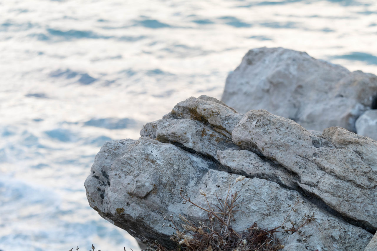 Close-Up Of Rocks On Shore Against Sky