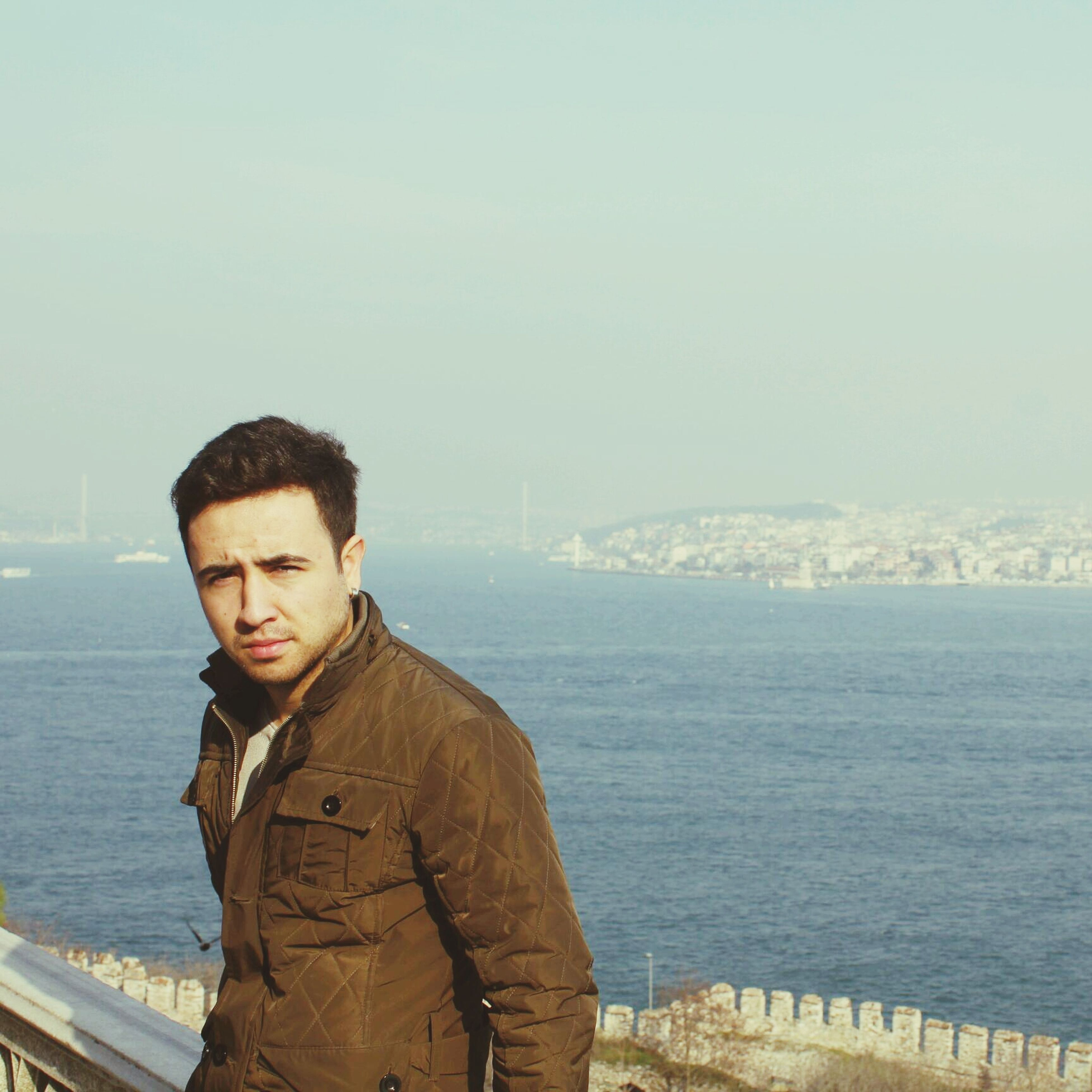 lifestyles, water, person, young adult, young men, leisure activity, casual clothing, standing, looking at camera, smiling, sea, portrait, waist up, three quarter length, clear sky, front view, sky