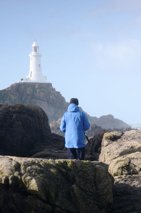 A photographer prepares to take a picture of La Corbiere Lighthouse on Jersey in the Channel Islands Balance Blue Sky La Corbi Lighthouse Minimalist Photographer Portrait Positioning Recreational Pursuit Rocks Shadow Sunny Day Taking Photos Tall - High Telling Stories Differently