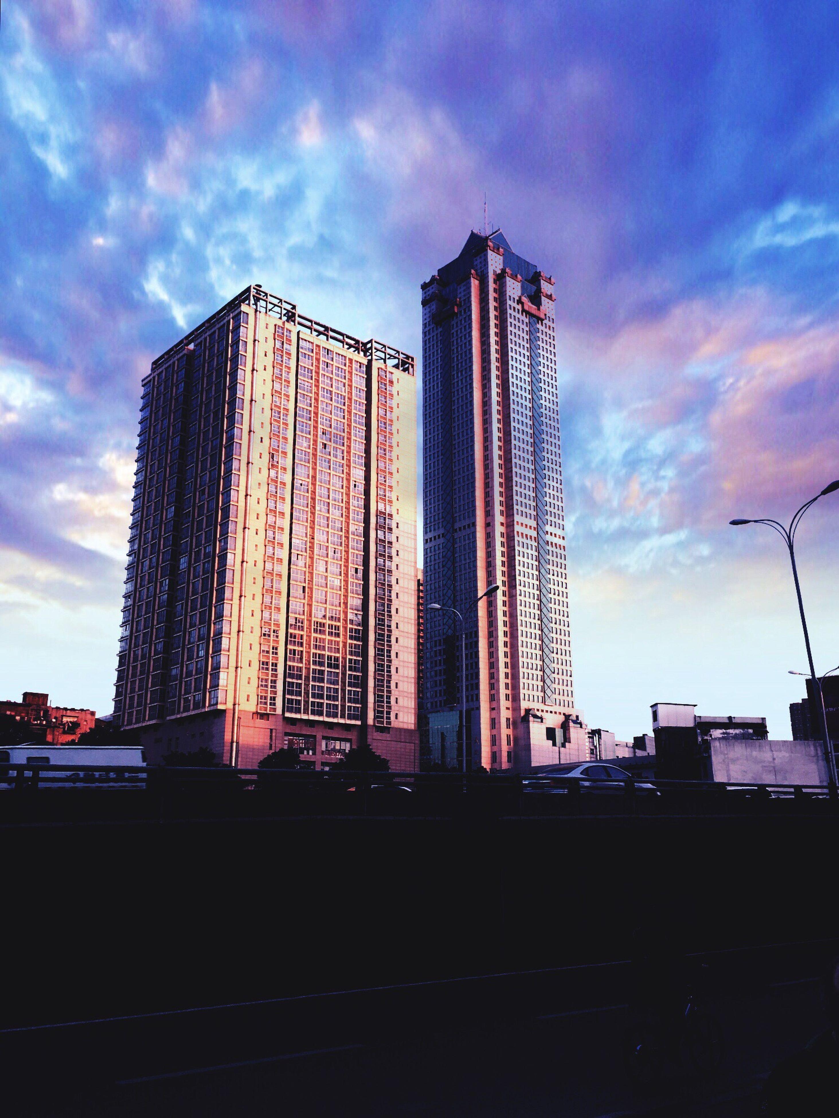 city, architecture, sky, skyscraper, building exterior, low angle view, built structure, urban skyline, outdoors, no people, cloud - sky, cityscape, suspension bridge, day