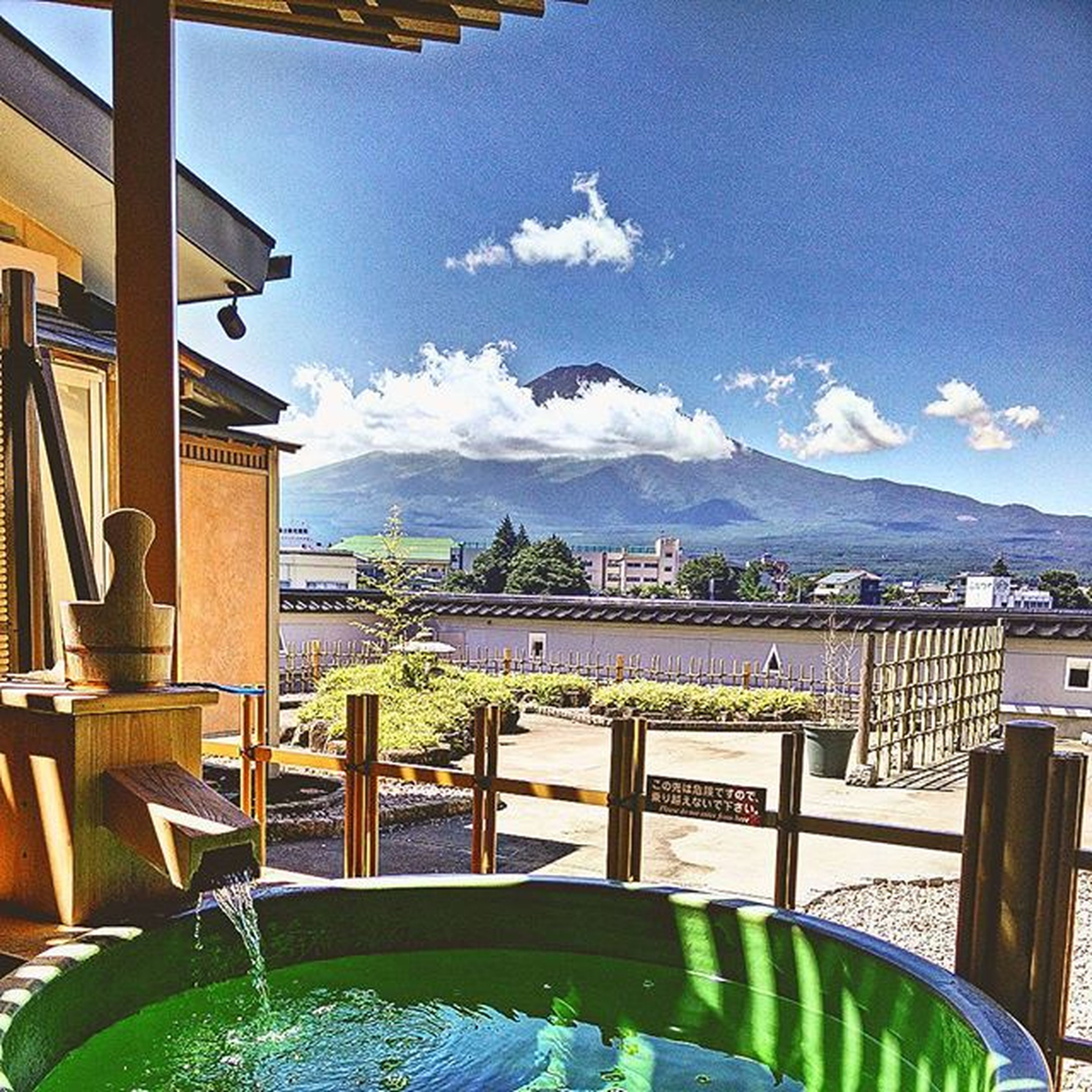 mountain, architecture, sky, built structure, building exterior, cloud - sky, mountain range, table, railing, window, cloud, water, day, indoors, sea, blue, chair, city, balcony, house
