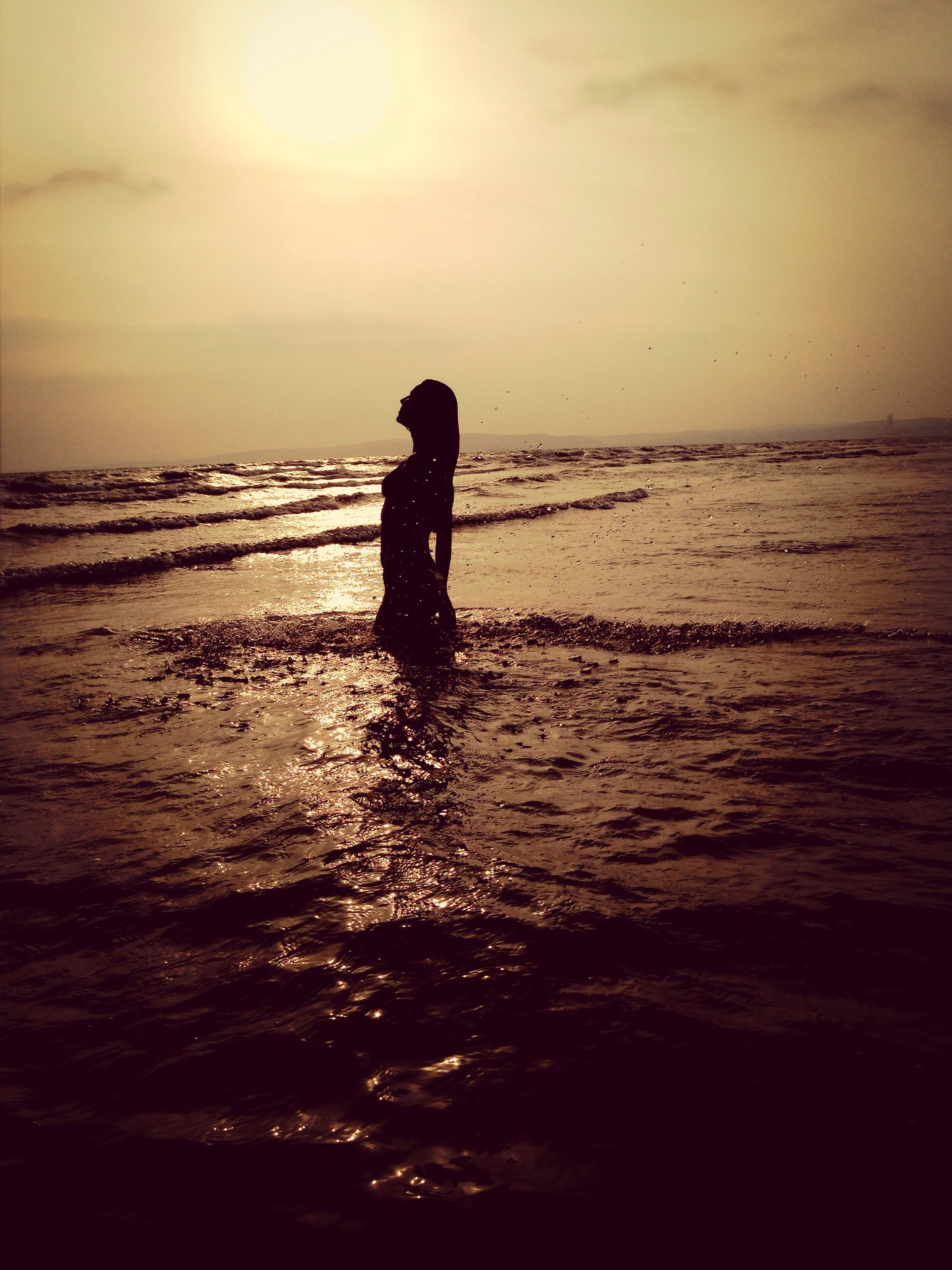 sea, water, horizon over water, sunset, silhouette, beach, scenics, sky, tranquil scene, tranquility, beauty in nature, shore, one person, nature, idyllic, reflection, standing, wave, dusk, sun