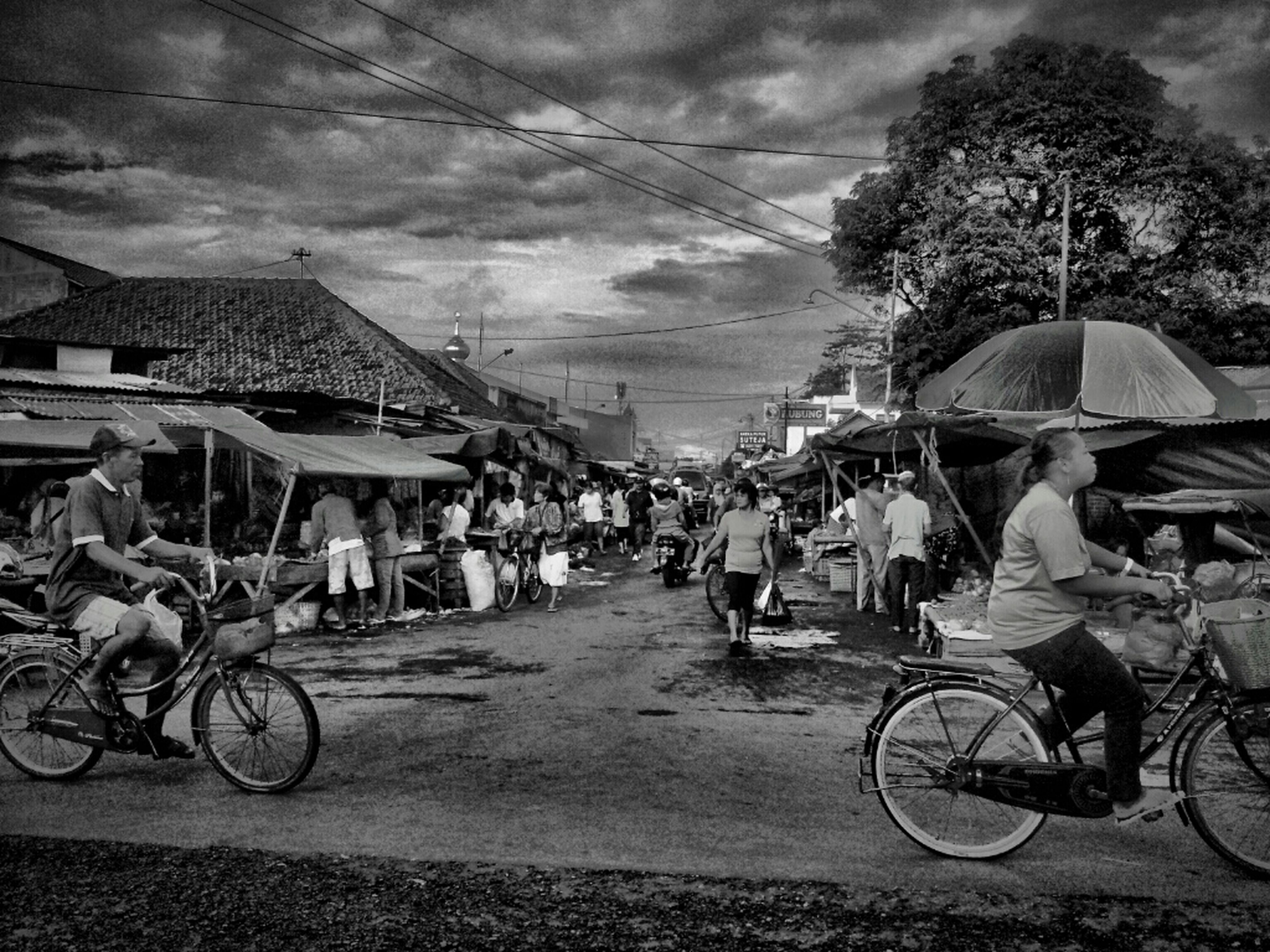 bicycle, transportation, mode of transport, land vehicle, sky, parking, parked, building exterior, architecture, stationary, street, built structure, men, cloud - sky, tree, travel, person, cobblestone, large group of people