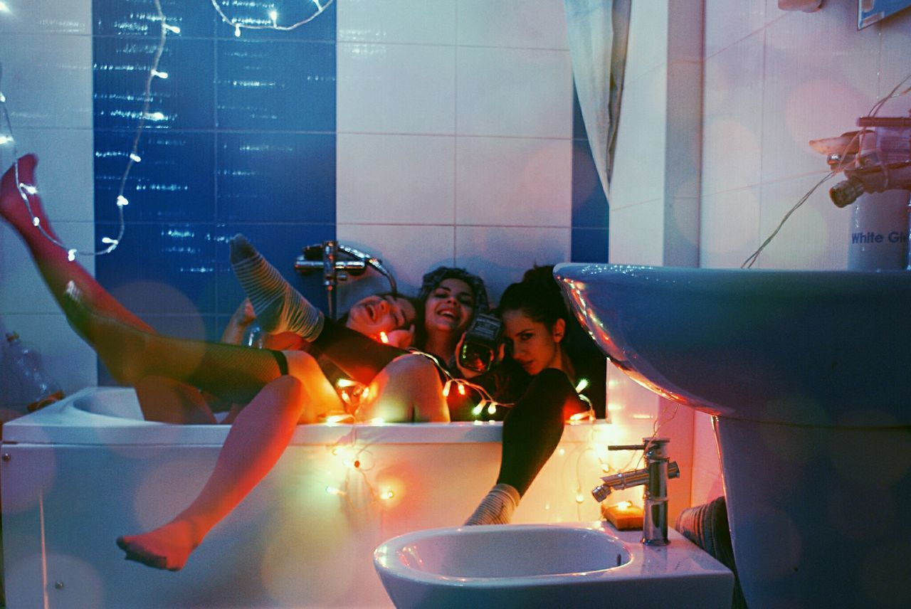 real people, lifestyles, boys, leisure activity, togetherness, indoors, water, fun, domestic bathroom, enjoyment, childhood, happiness, illuminated, bathroom, standing, bonding, men, night, friendship, people