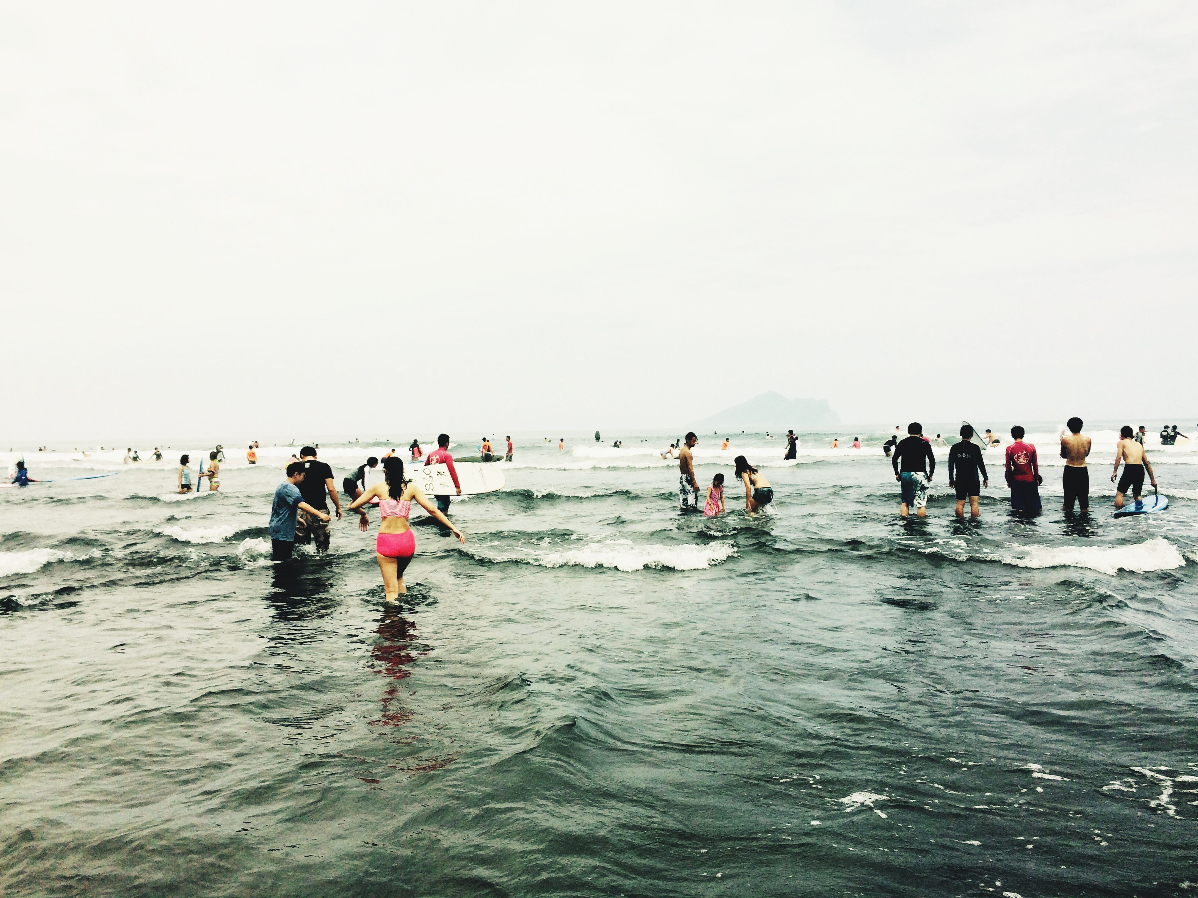 water, large group of people, sea, leisure activity, beach, lifestyles, vacations, clear sky, enjoyment, mixed age range, copy space, men, horizon over water, person, waterfront, shore, fun, tourist, enjoying