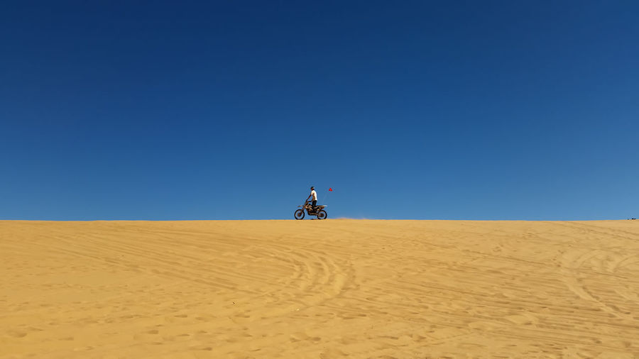 Dirt bike rider at the top of a sand dune Coral Pink Sand Dunes State Park Motorbike Rider Motorcycle Navajo Sandstone Utah Adventure Arid Climate Clear Sky Desert Desert Beauty Dirt Bike Rider Extreme Sports Horizon Over Land Landscape Motorsports negative space One Person Outdoors Remote Sand Sand Dune Sand Dunes Scenics Solitude Travel Destinations An Eye For Travel