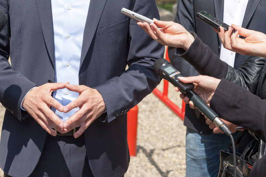 Media interview. News conference. Media Report Business Interview Journalist Press Answering Asking Businessman Businessperson Comment Conference Gesture Gesturing Hand Information Journalism Microphone News People Politician Question Reporter