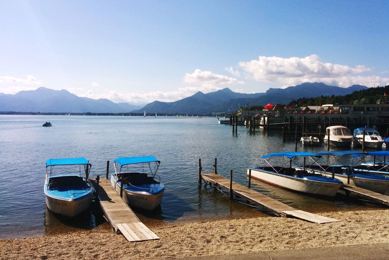 mountain, water, sky, nature, scenics, nautical vessel, outdoors, mountain range, day, moored, beauty in nature, transportation, no people, tranquil scene, sea, tranquility, blue, travel destinations, built structure, harbor, architecture