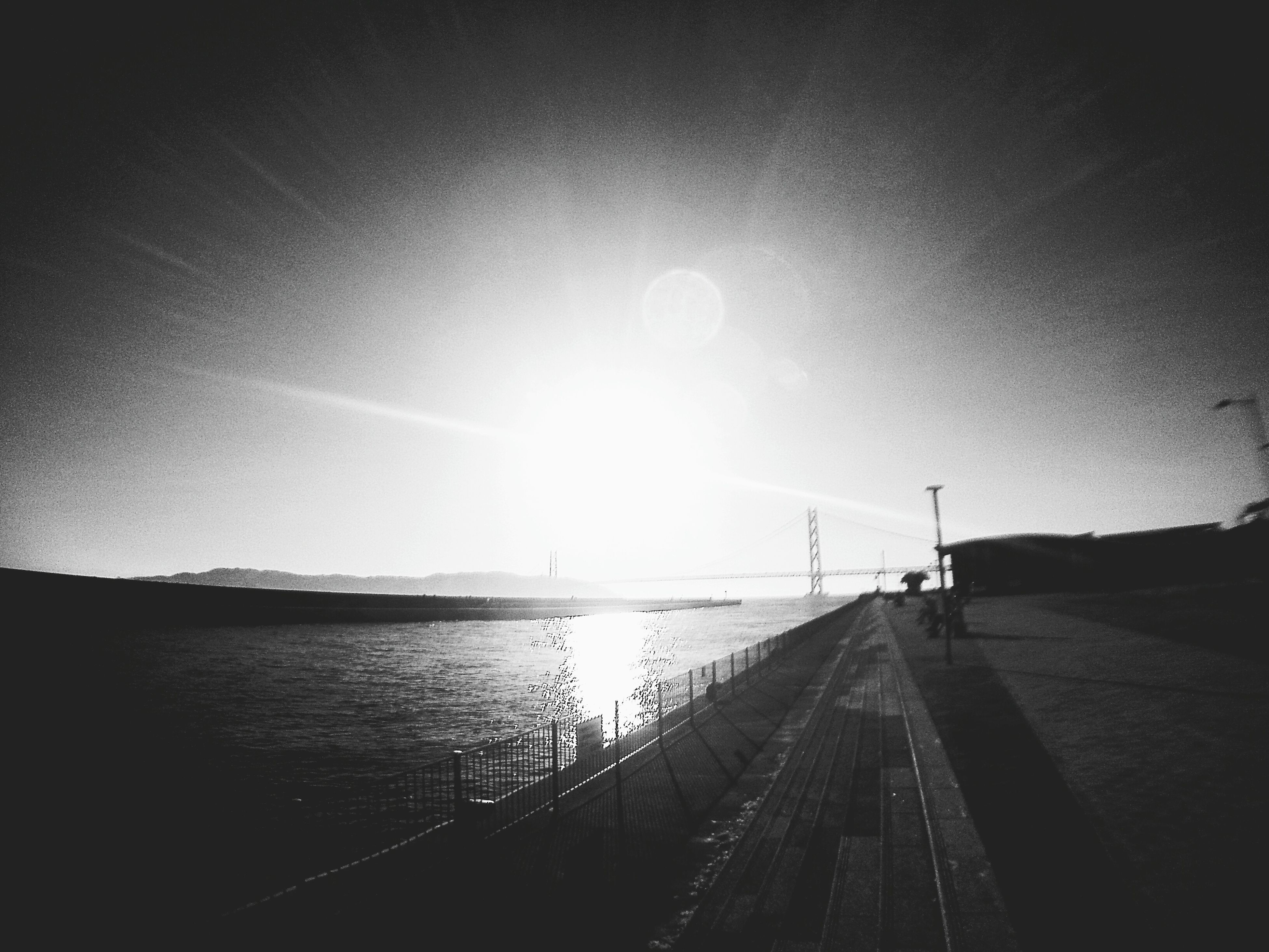 the way forward, sun, sky, water, transportation, diminishing perspective, sunlight, vanishing point, sunbeam, nature, sunset, tranquility, silhouette, road, outdoors, lens flare, tranquil scene, no people, beauty in nature, railing