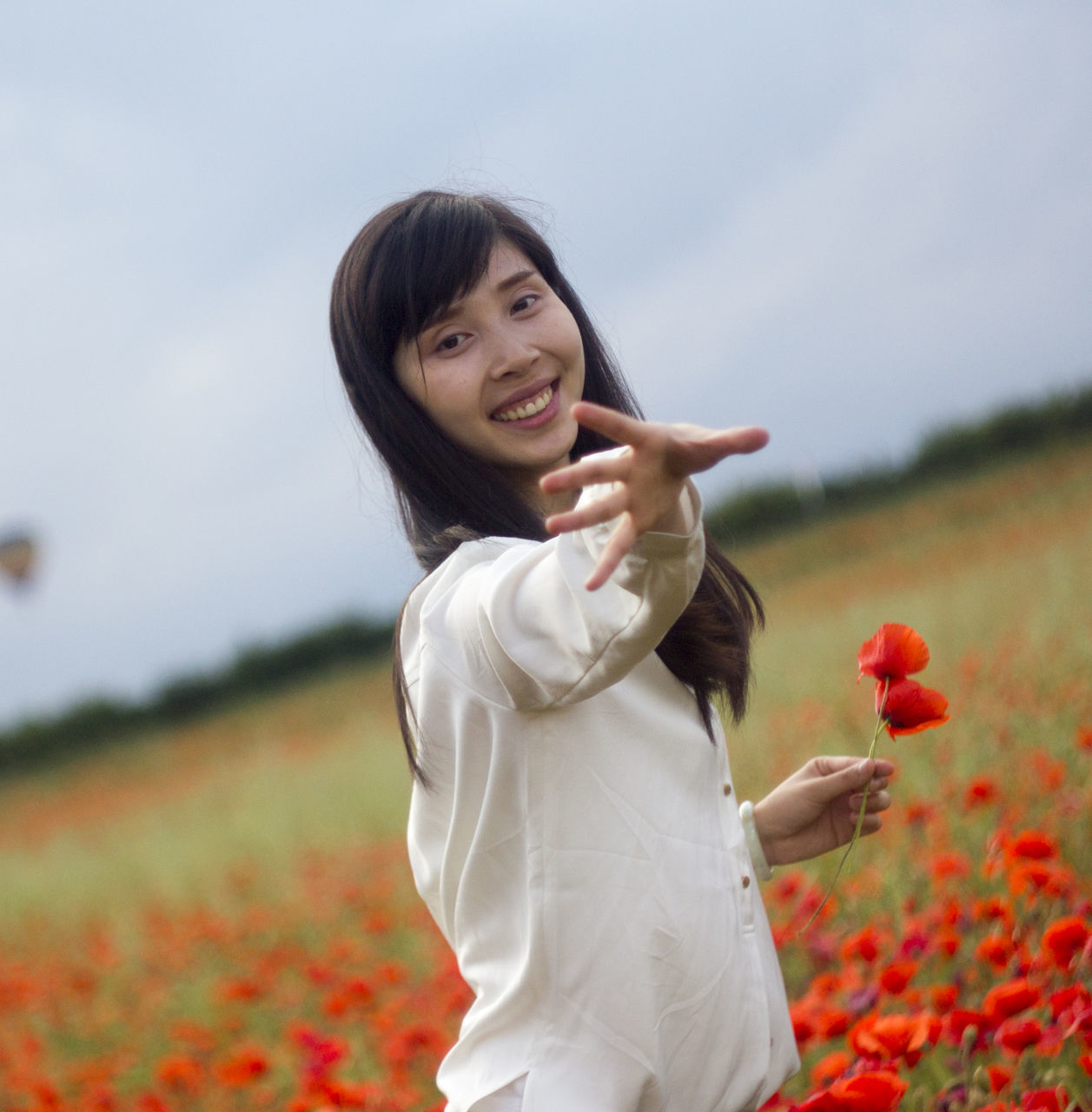 Portrait Of Young Smiling Woman Gesturing On Poppy Field Against Sky
