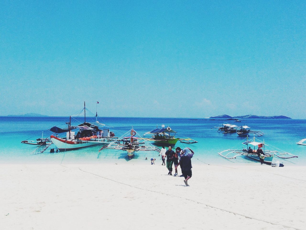 sea, beach, water, nautical vessel, transportation, shore, real people, horizon over water, sand, scenics, men, mode of transport, nature, full length, moored, day, fisherman, beauty in nature, outdoors, clear sky, sky, outrigger, blue, occupation, large group of people, longtail boat, jet boat, adult, people