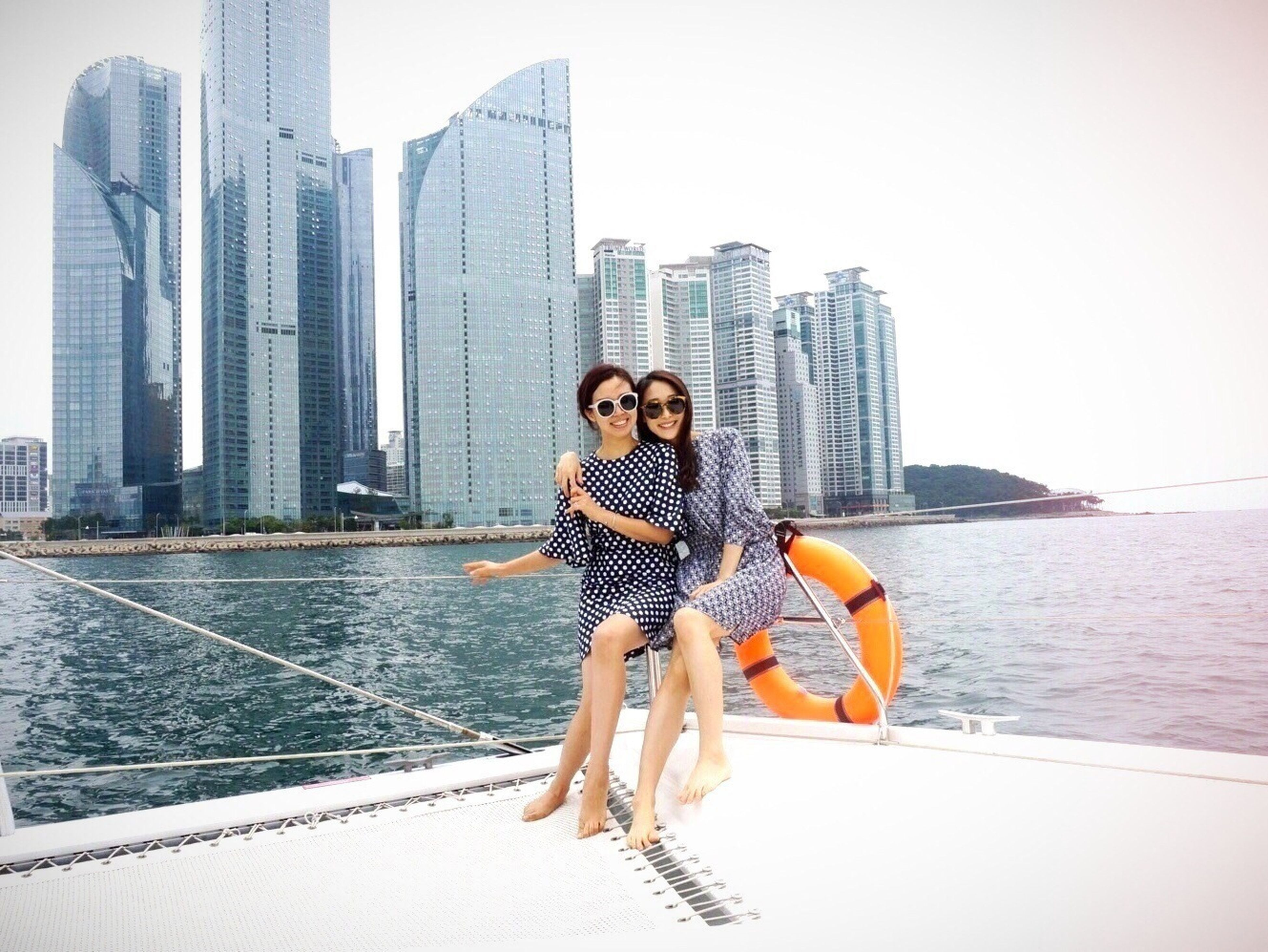 young adult, person, lifestyles, casual clothing, looking at camera, front view, portrait, leisure activity, standing, young women, smiling, full length, water, building exterior, happiness, three quarter length, built structure, sunglasses