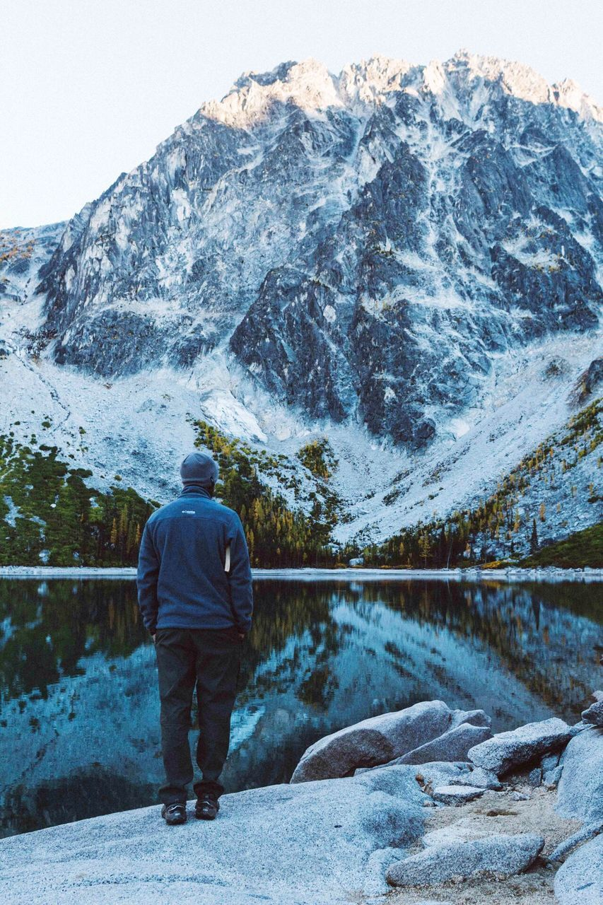 Rear View Of Man Standing On Rock Looking At Snowcapped Mountain By Lake