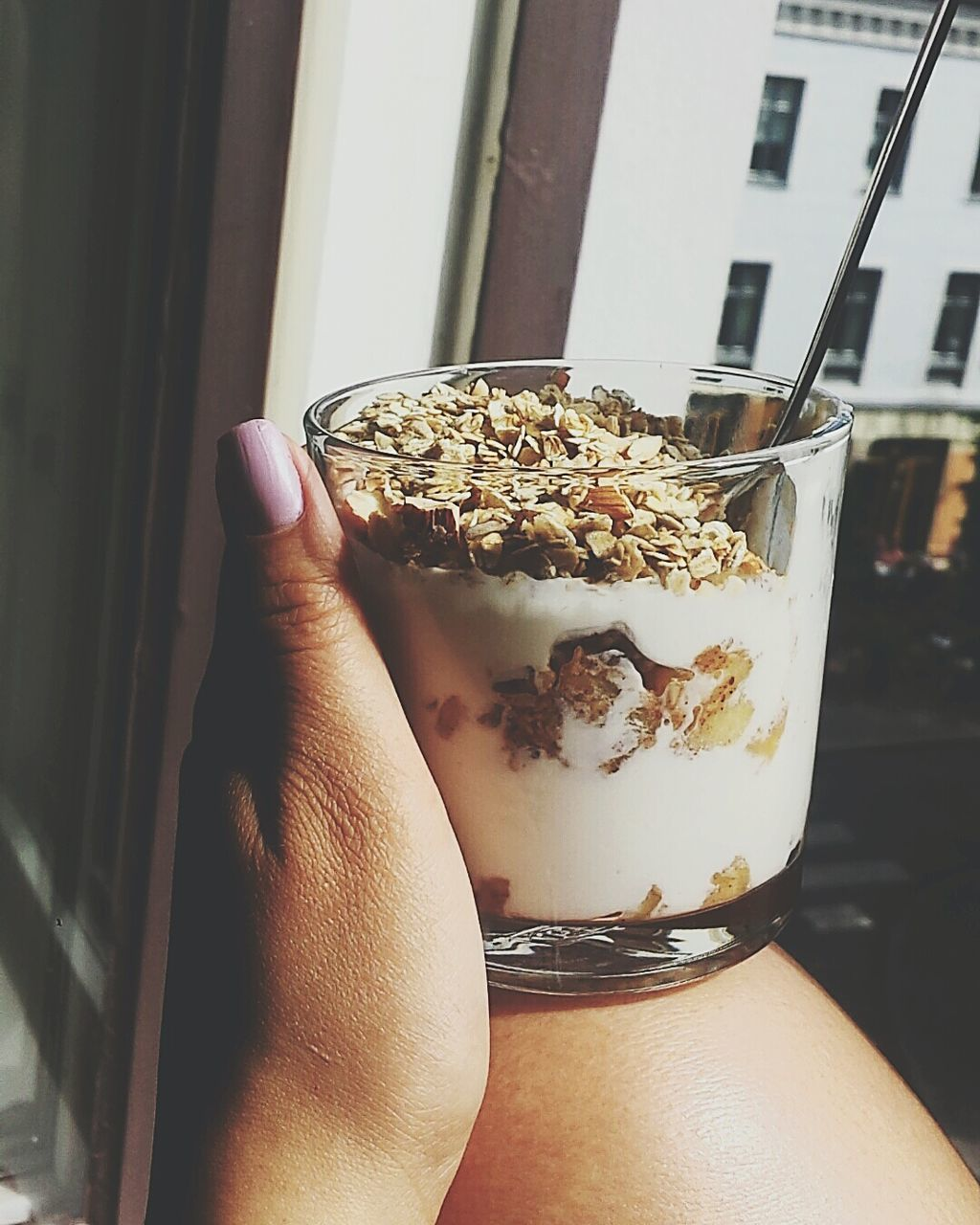 Cropped Image Of Hand Holding Muesli And Milk Glass At Home