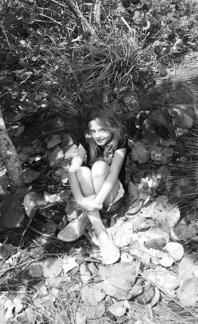 Girl Young Girl Sitting Down In The Forest In The Brush Blonde Girl Playing With The Light Playing With The Shadows Grin Smirk Portrait Of A Friend Black And White Photography Black And White Portrait