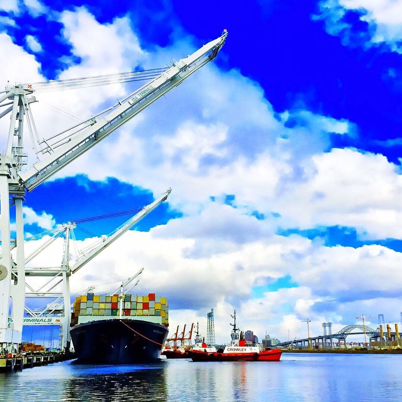 transportation, nautical vessel, sky, cloud - sky, mode of transport, water, waterfront, freight transportation, river, day, outdoors, commercial dock, crane - construction machinery, no people, shipping, harbor, built structure, moored, cargo container, architecture, nature, industry, sailing, beauty in nature, shipyard