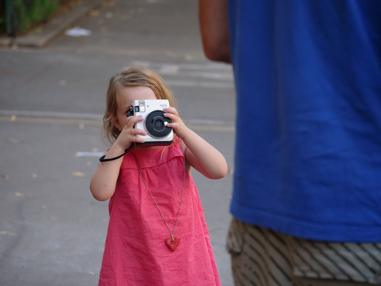 camera - photographic equipment, photography themes, photographing, real people, leisure activity, digital camera, photographer, digital single-lens reflex camera, childhood, technology, holding, girls, two people, outdoors, day, slr camera, casual clothing, camera, front view, lifestyles, togetherness, standing