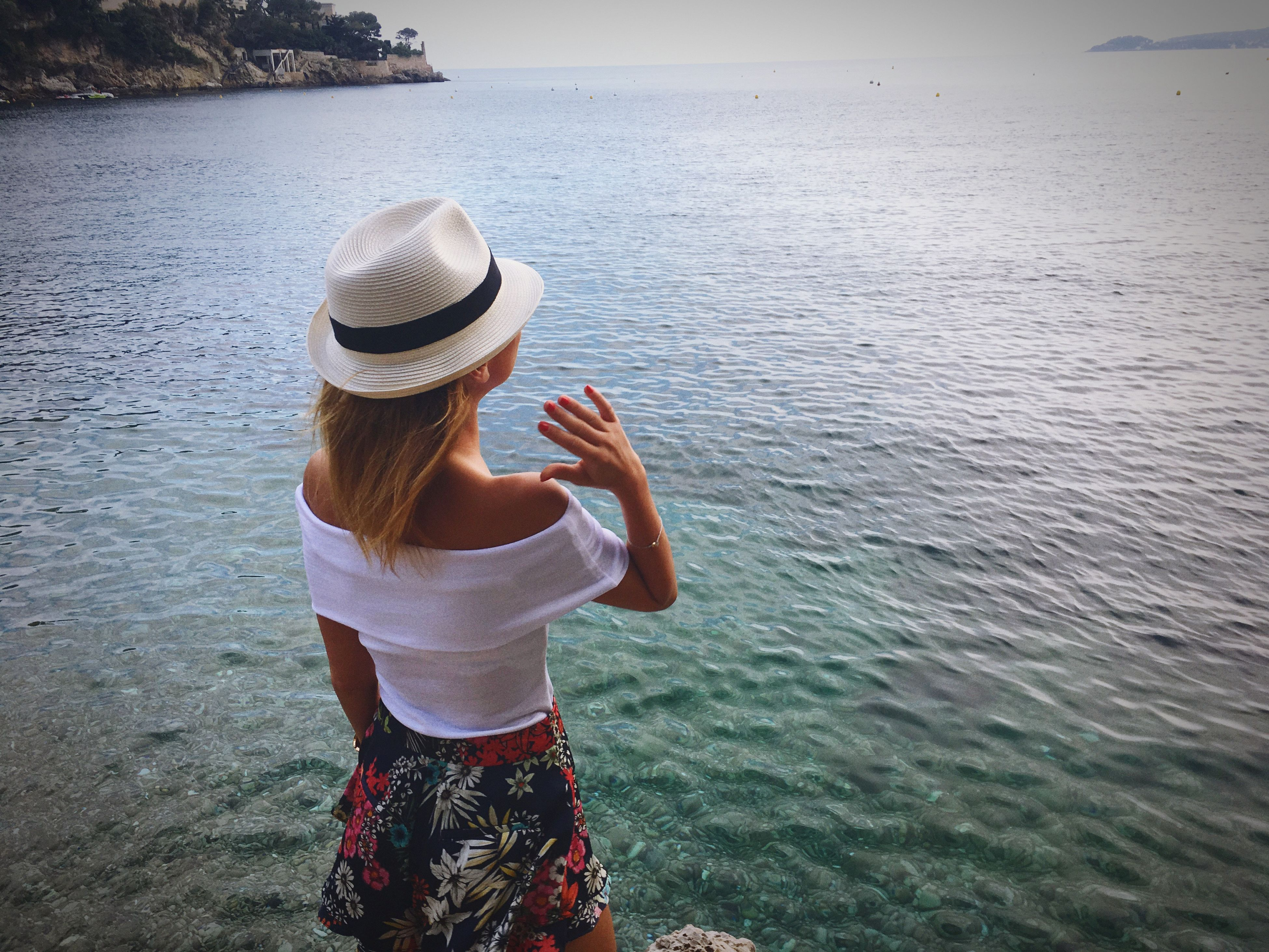 real people, leisure activity, water, one person, hat, lifestyles, three quarter length, rear view, casual clothing, sea, beauty in nature, standing, day, nature, outdoors, vacations, sun hat, women, scenics, young adult, young women