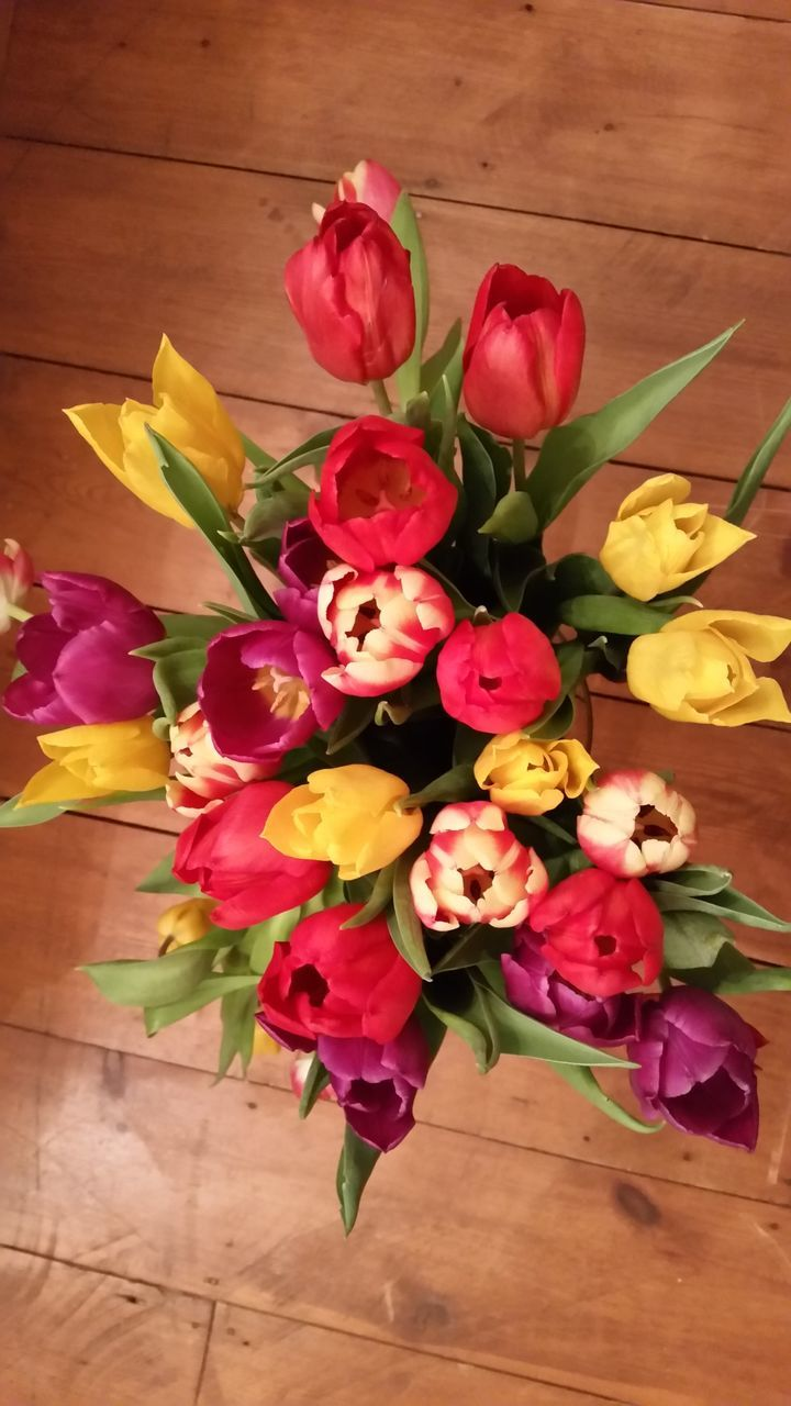 High Angle View Of Various Tulips In Vase On Hardwood Floor