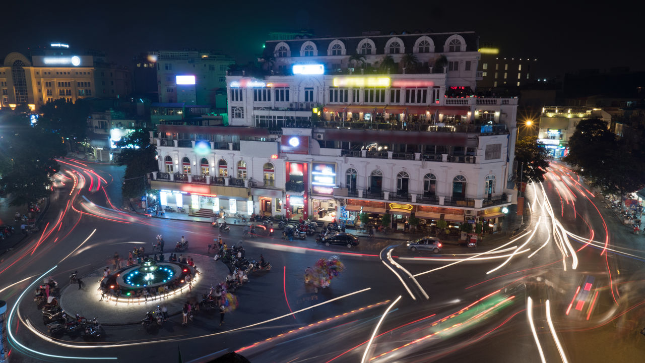 City view with transport in motion at night. Red and white trails on the square with people and bikes at the fountain Cguare City City Life City Street Dynamic Fountain Hanoi Highway Horizontal Illuminated Motorcycle Night Nightlife Outdoors Road Speed Street Traffic Traffic Transportation Vietnam