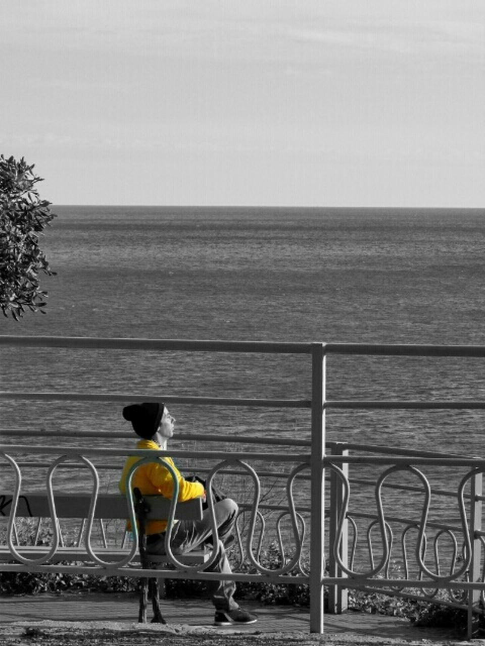 sea, railing, water, real people, one person, horizon over water, outdoors, rear view, day, standing, bicycle, men, yellow, nature, full length, sky, beauty in nature, people