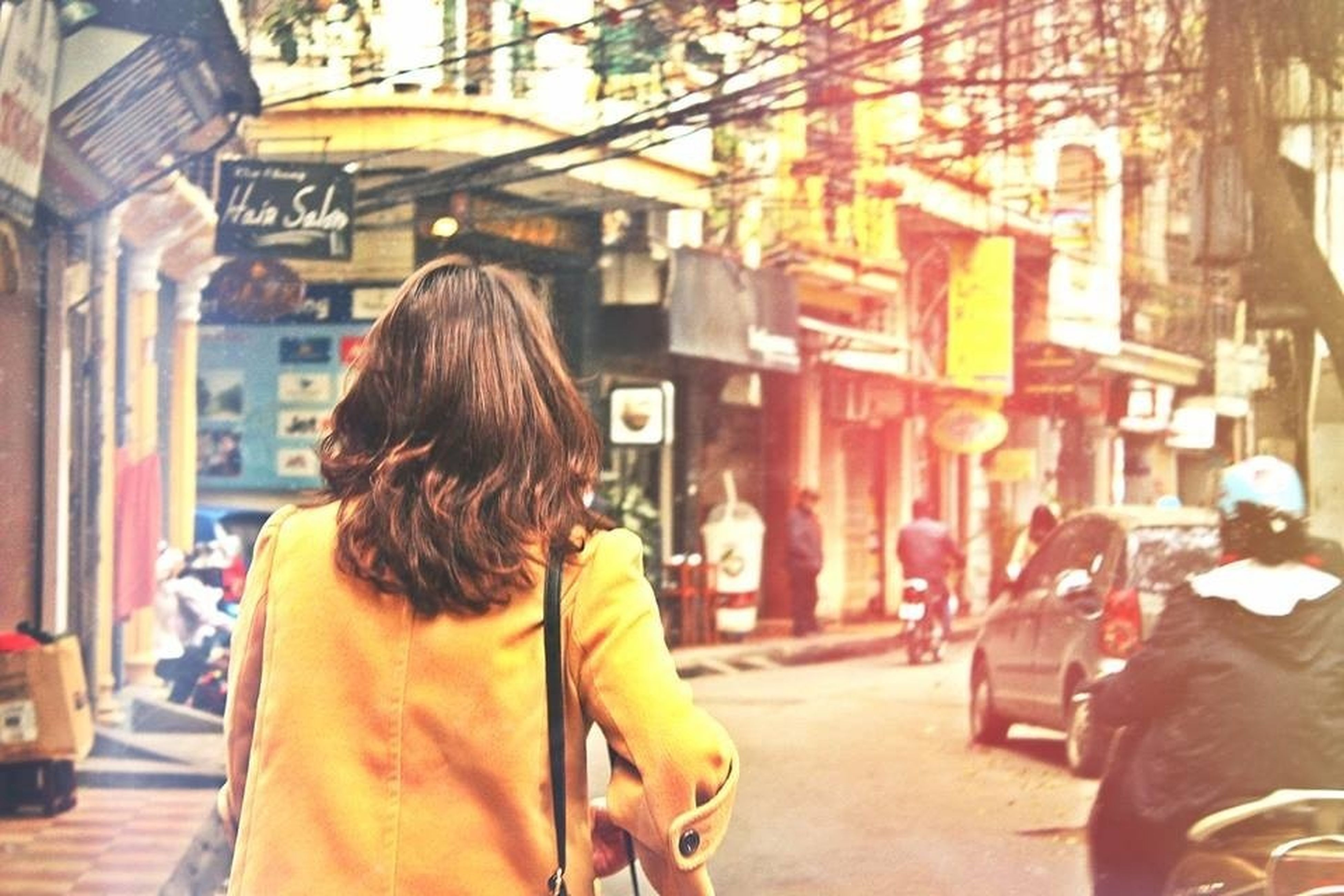 lifestyles, building exterior, architecture, person, built structure, rear view, leisure activity, city, street, incidental people, casual clothing, city life, focus on foreground, long hair, standing, walking, illuminated, young women