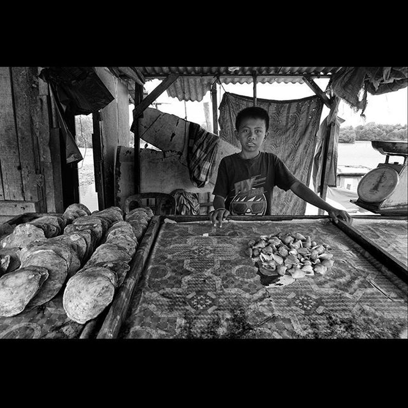 "This boy was a saler of big snail it's called ""Gonggong"" and big shell called ""Lokan"". the gonggong was only lived at Kepulauan Riau waters. Anak lelaki ini ialah seorang penjual siput besar yang biasa disebut ""Gonggong"" dan kerang besar disebut ""Lokan"". Gonggong hanya hidup di perairan Kepulauan Riau. Dailylife Wonderfulkepri  Explorekepri KepriBukanRiau Indonesia_photography Geonusantara Kompasnusantara Pewartafotoindonesia Natgeonesia 1000kata Wonderfulindonesia Serikat_fi IndonesiaOnly Photooftheday Thephotosociety Stagephoto Hipaae Hipasnap Blackandwhitephoto Bw_indonesia Artphoto_bw Bnw_globe Bnw_worldwide Bestshooter_bw Monochrome FujiGuysID"
