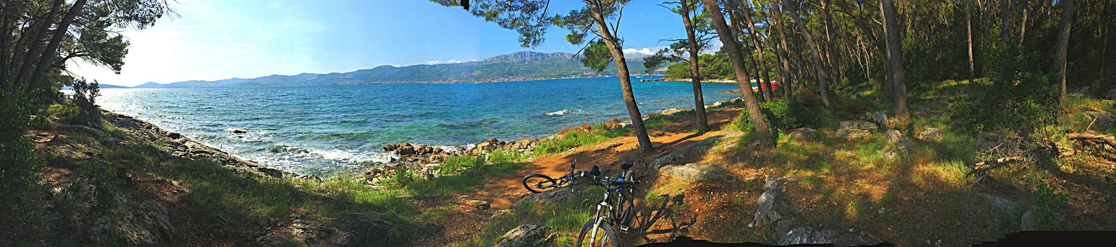 water, tranquil scene, tranquility, sea, scenics, beauty in nature, mountain, beach, nature, sky, tree, shore, idyllic, coastline, non-urban scene, sunlight, day, horizon over water, sand, blue