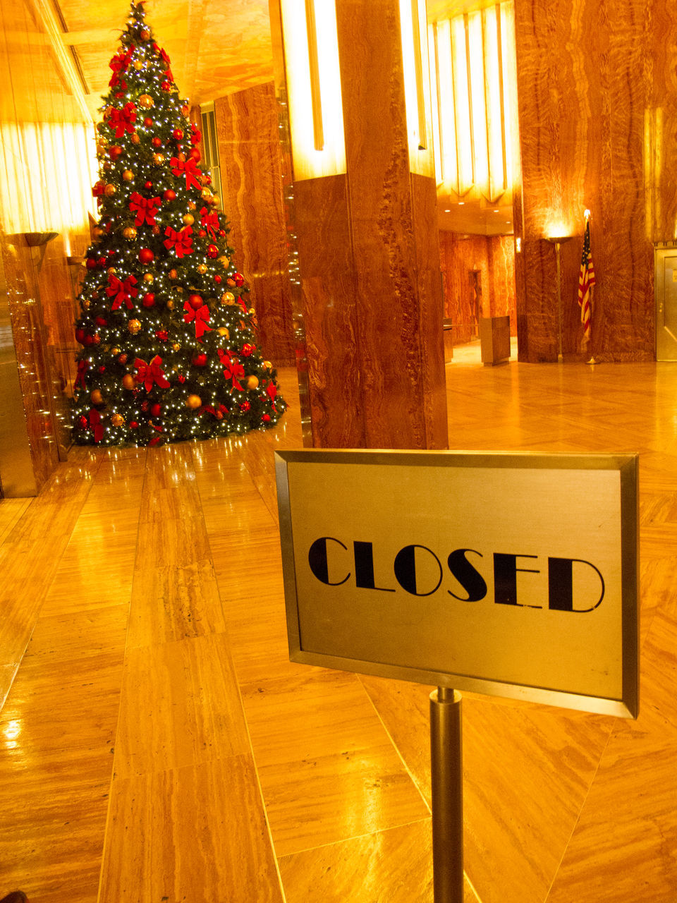 Closed sign in front of decorated Christmas tree in building
