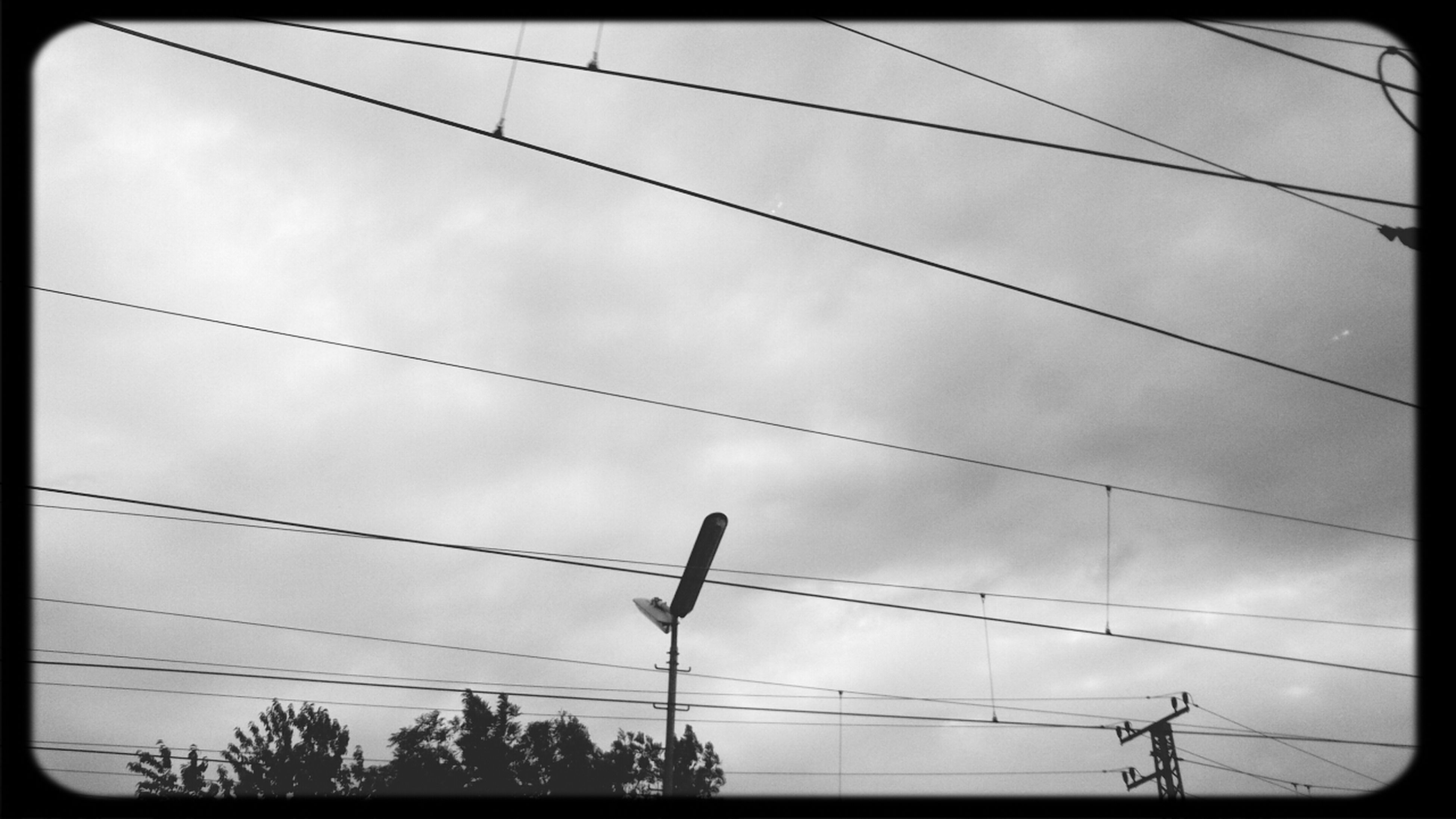 power line, low angle view, cable, power supply, electricity, electricity pylon, transfer print, sky, connection, auto post production filter, silhouette, power cable, cloud - sky, fuel and power generation, technology, cloudy, cloud, tree, outdoors, no people
